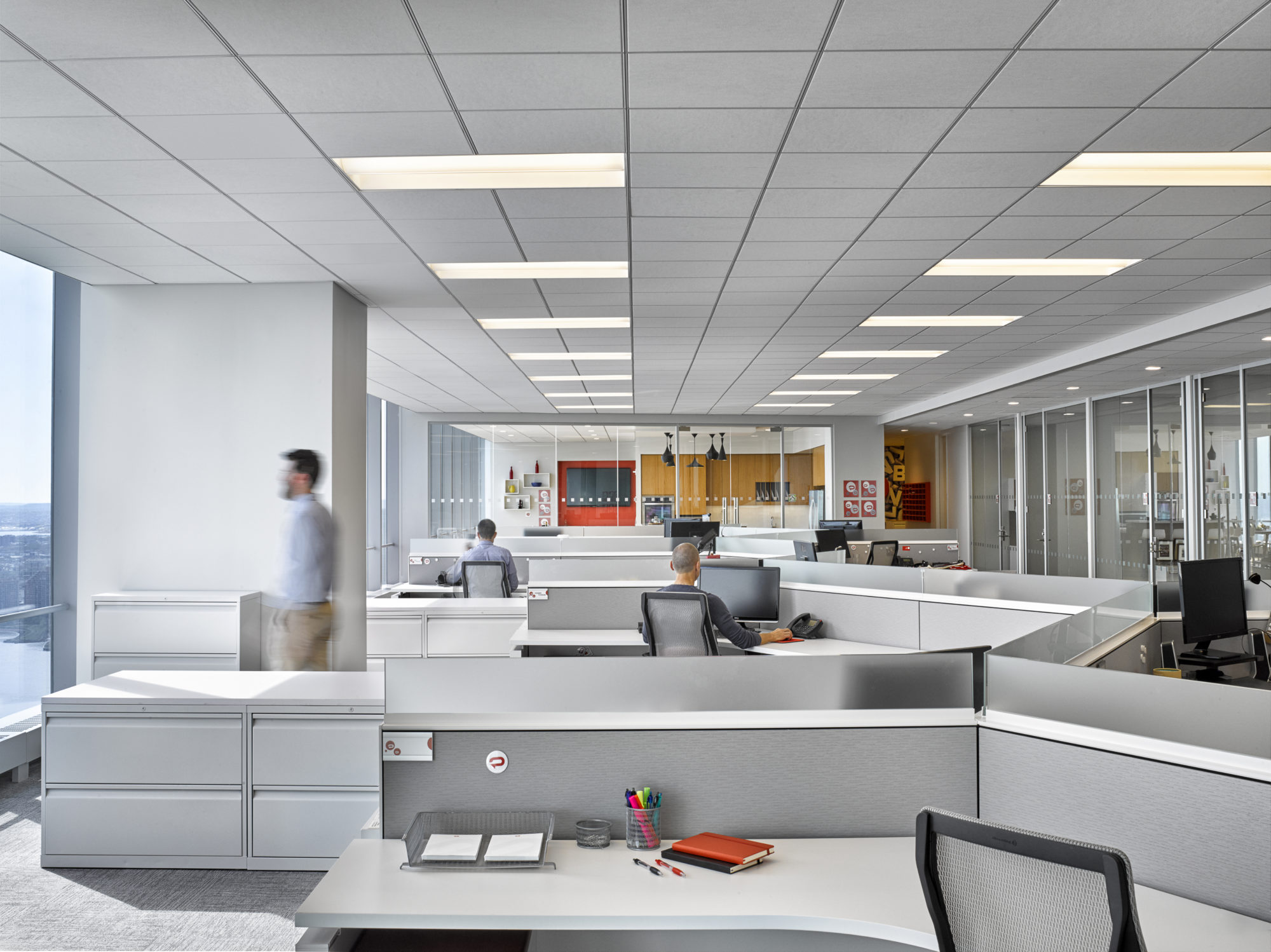 Man looking out the window as people work at their desks in the offices of Padilla CRT in New York. MEP designed by 2L Engineering.