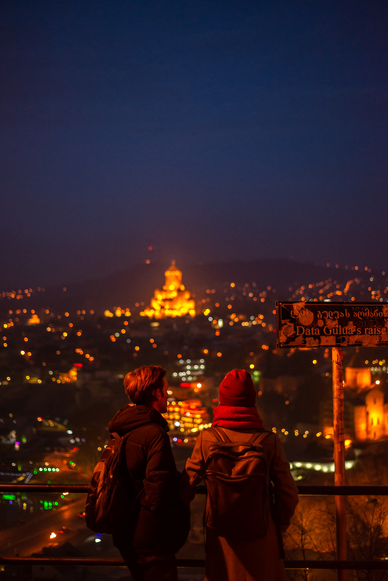 A young couple enjoying Tbilisi by night from a nearby hill.