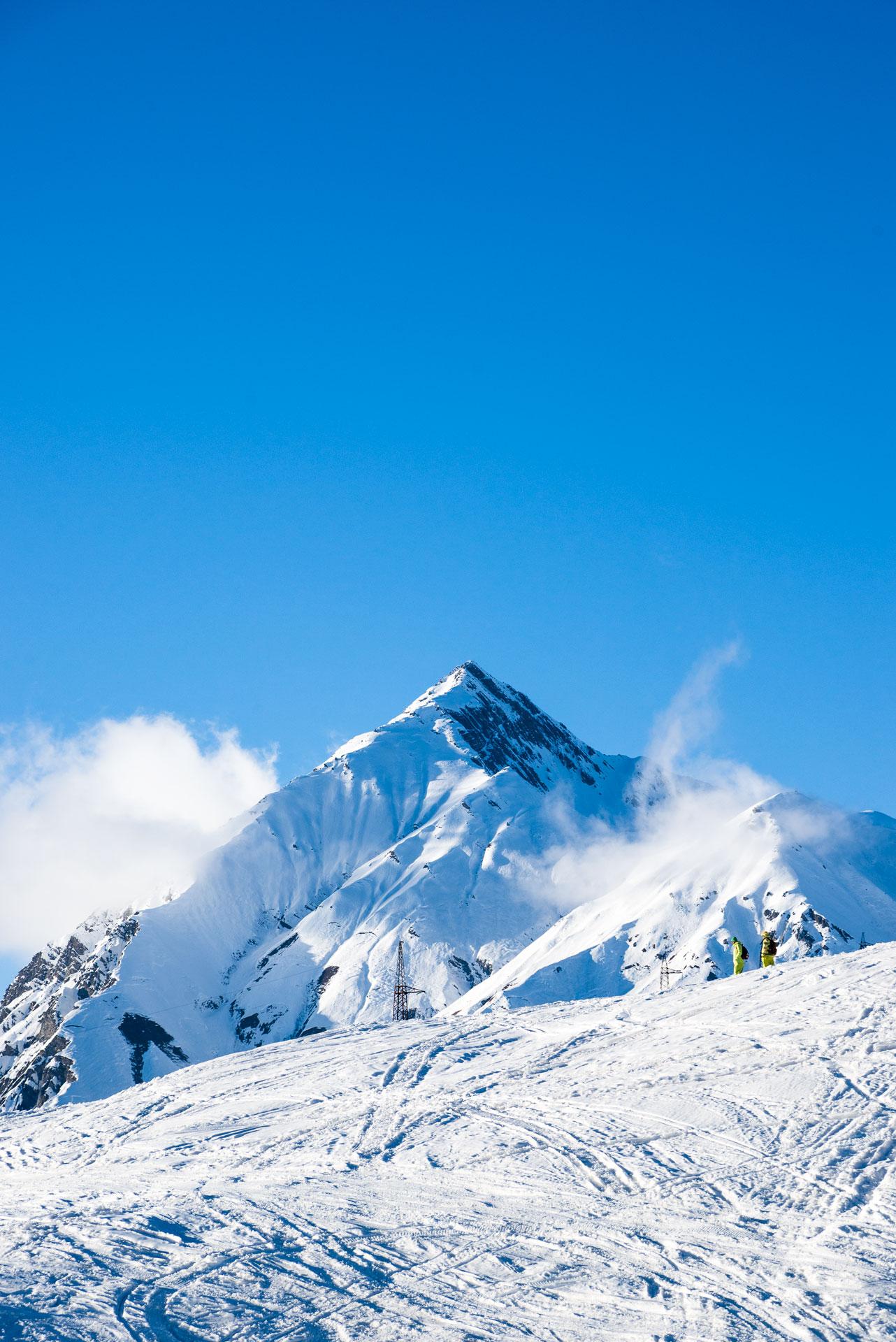 Two skiers walking close to one of the peaks in Gudauri.
