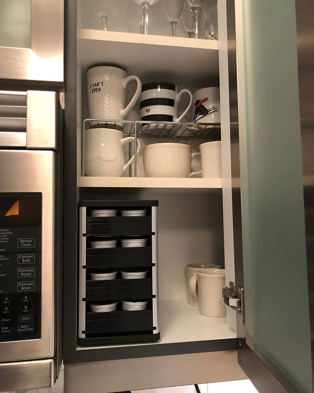 We utilized every inch of cupboard space in this clients New York City apartment with this k-cup organizer. The drawers pull out and down so it's easy for her to select her coffee despite it being in an upper cupboard. #organized #organizing #shelfspaceorganizing #keurig #coffeestation # smallspaces #apartmentorganizing