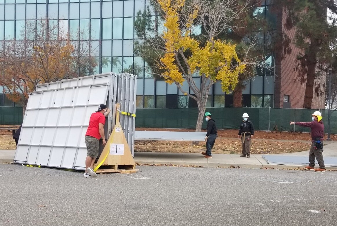 San Jose Conservation Corps crew begin unloading the panels of a Pallet shelter.