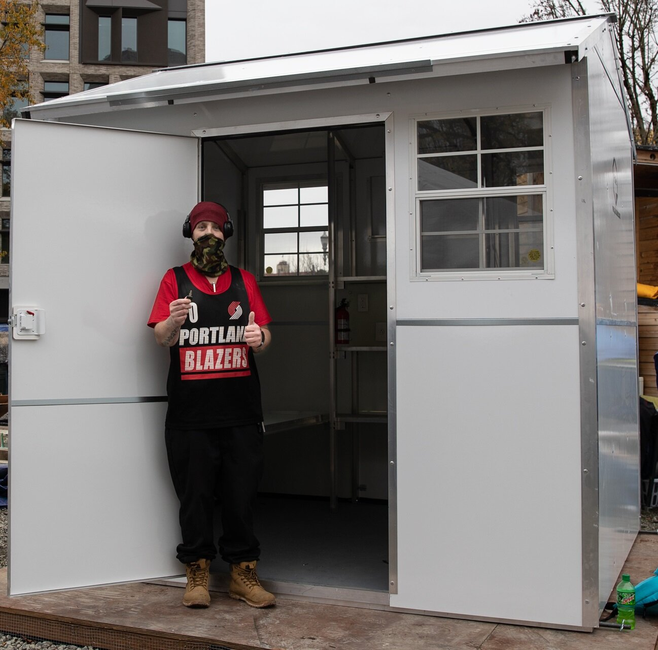 CP3O Village in Portland opened in November 2020. A resident holds up a key to the Pallet shelter they're going to stay in temporarily. Photo credit: Multnomah County