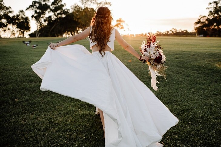 bride running across a field at sunset with a flowy wedding dress blowing in the breeze