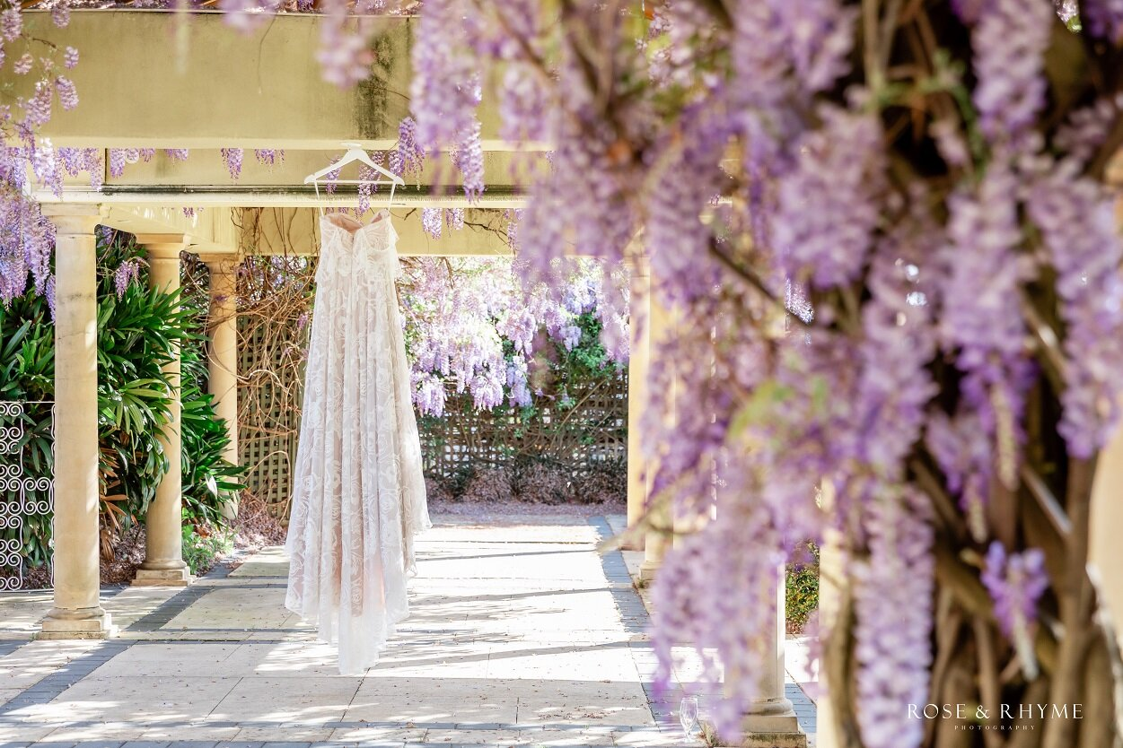 off-the-shoulder coffee-coloured wedding gown hanging amongst purple wisteria