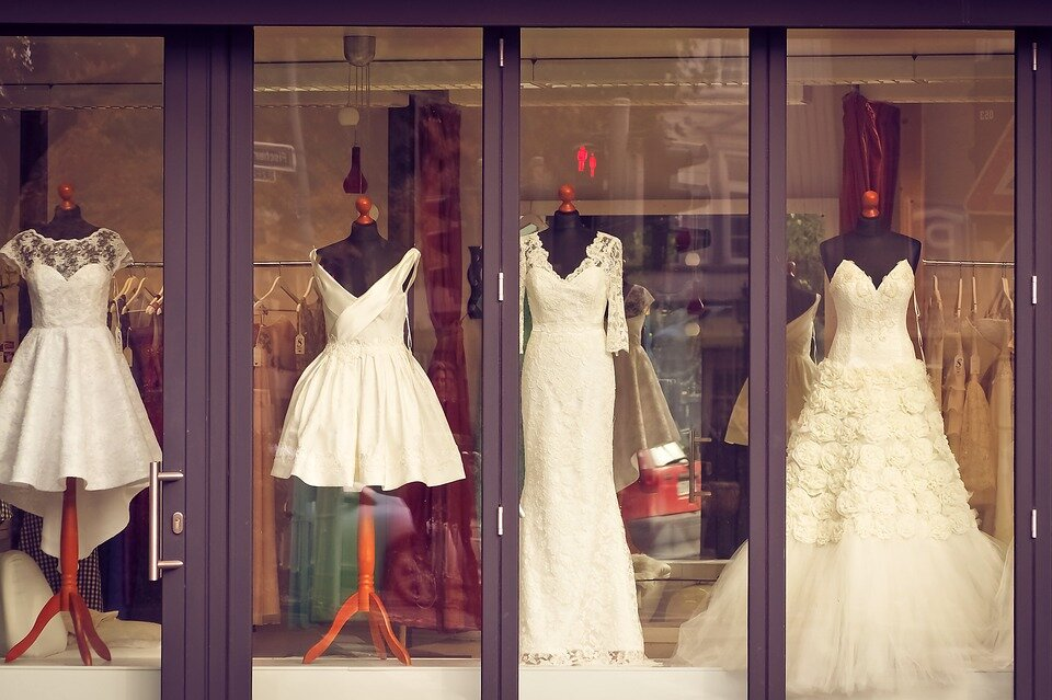 variety of pre-loved wedding dresses on display in a shop window