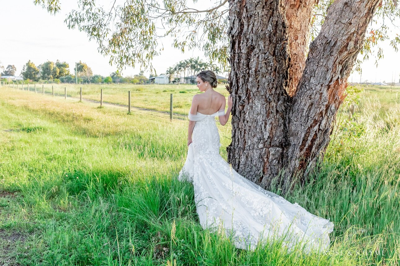 bride wearing off-the-shoulder gown standing in long grass by a tree