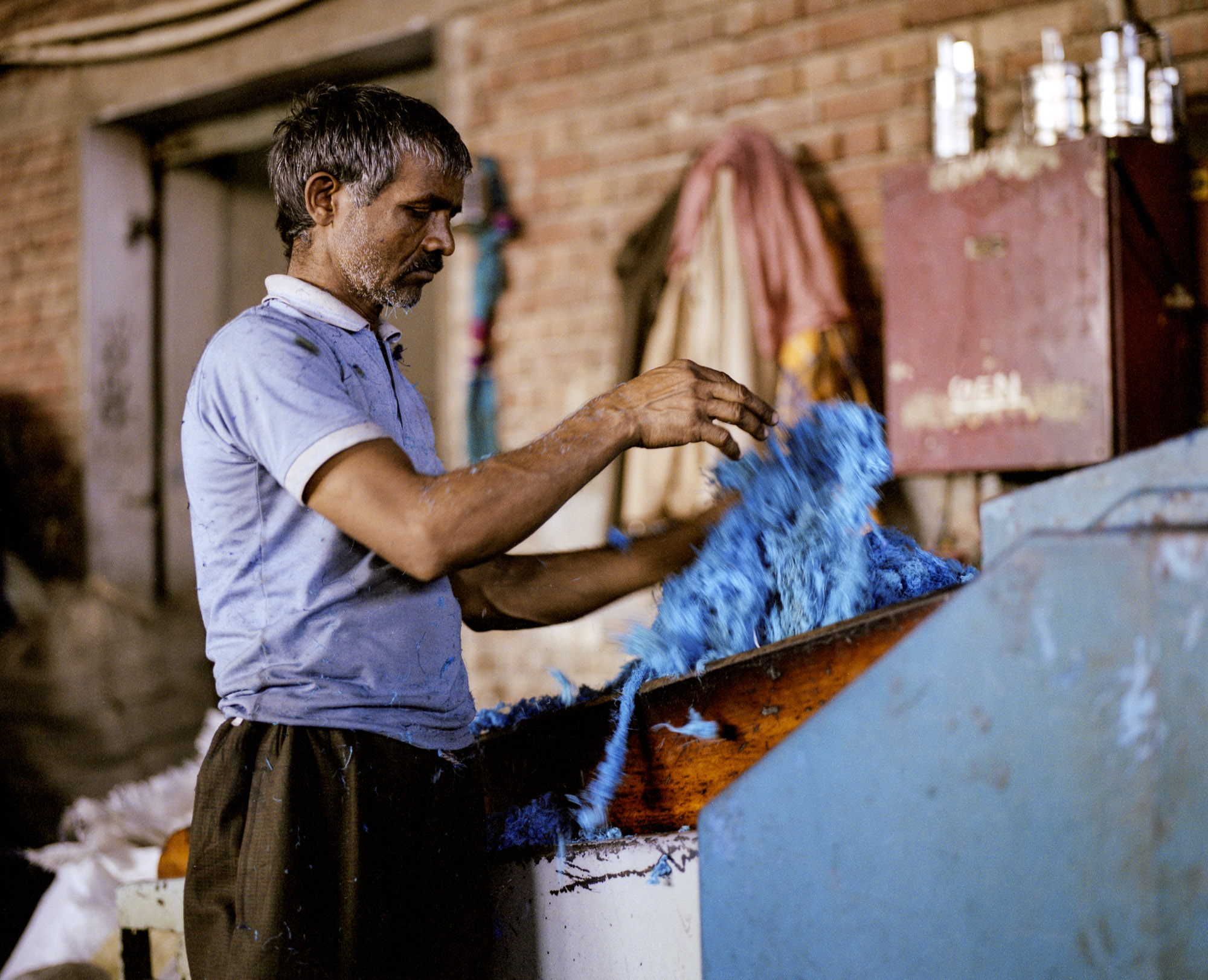 """Cavernous sheds are filled with old machines which break down the knitted and woven clothing into pulp, a source of reclaimed woolen and wool-mix fibres known as """"shoddy""""."""