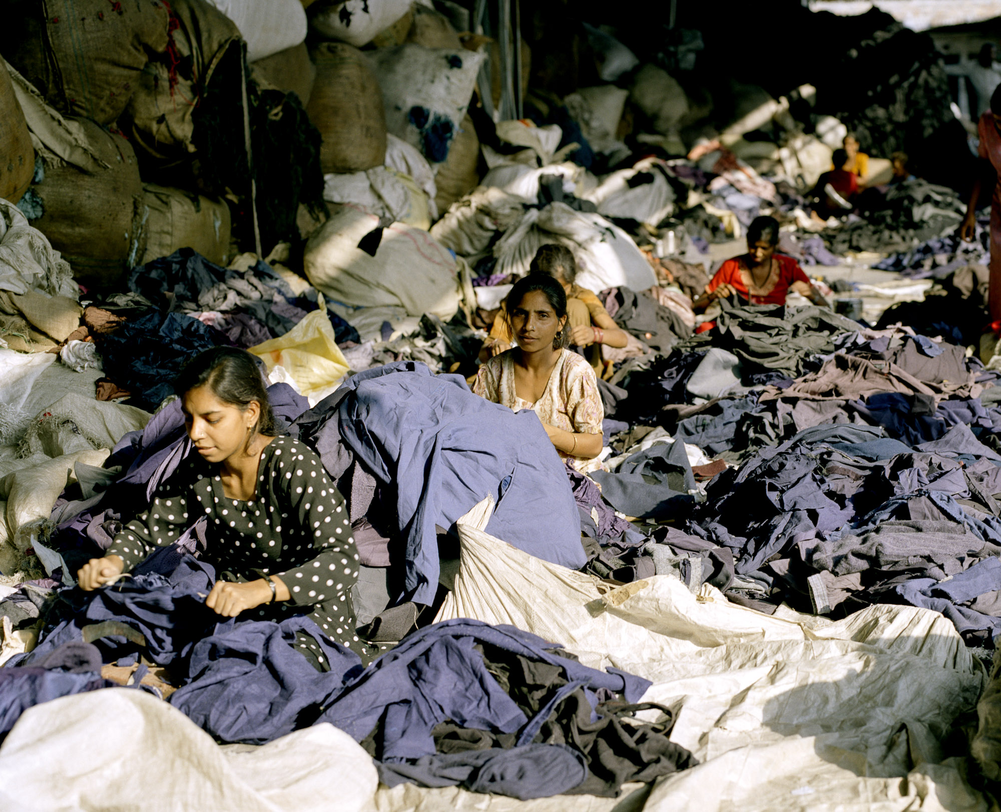 Women cut up jumpers, jackets and coats using traditional vegetable cutters. Garment labels advertising expensive brand names and global origins are discarded as worthless information.
