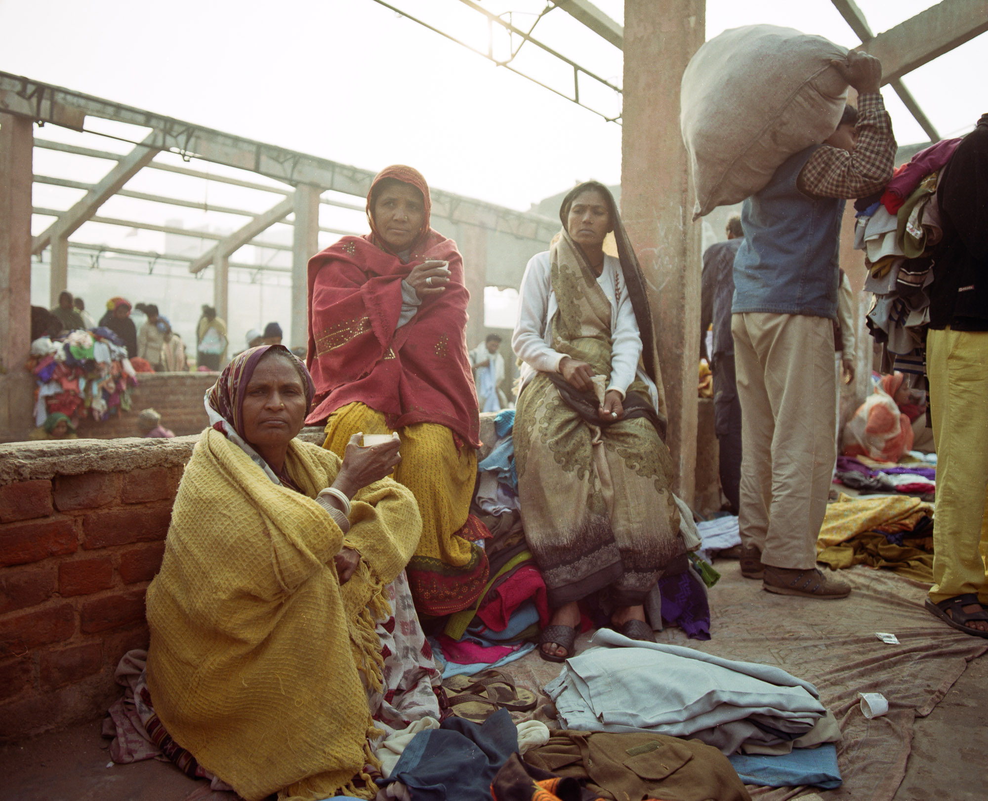 Women drinking chai on a December morning. Families often work together, traveling to their regular suburban patches to barter for clothes and selling them together at the market.