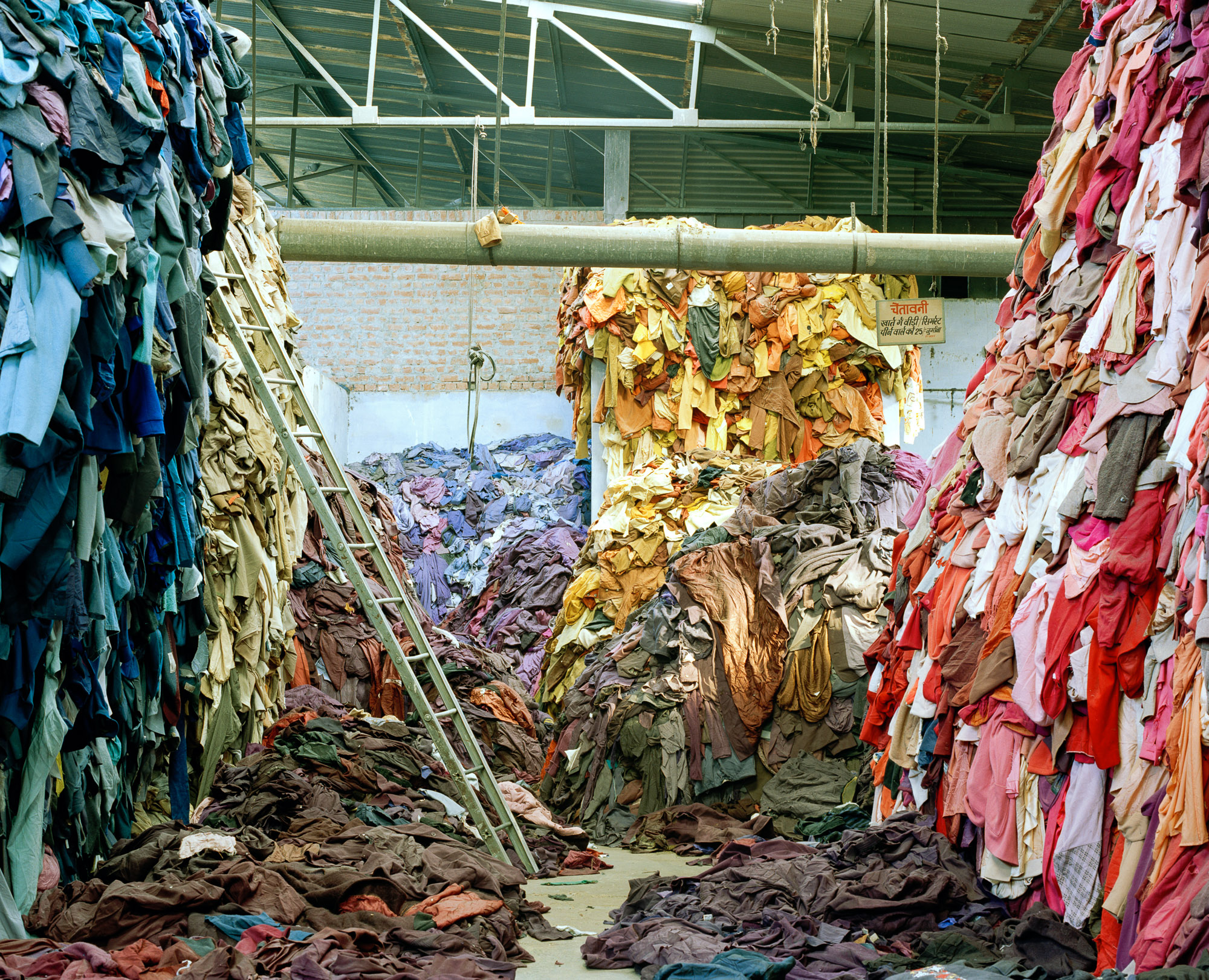 Cast-off woolen clothing is sorted again in large warehouses in Panipat, now into basic colour groups, where it's new value lies.