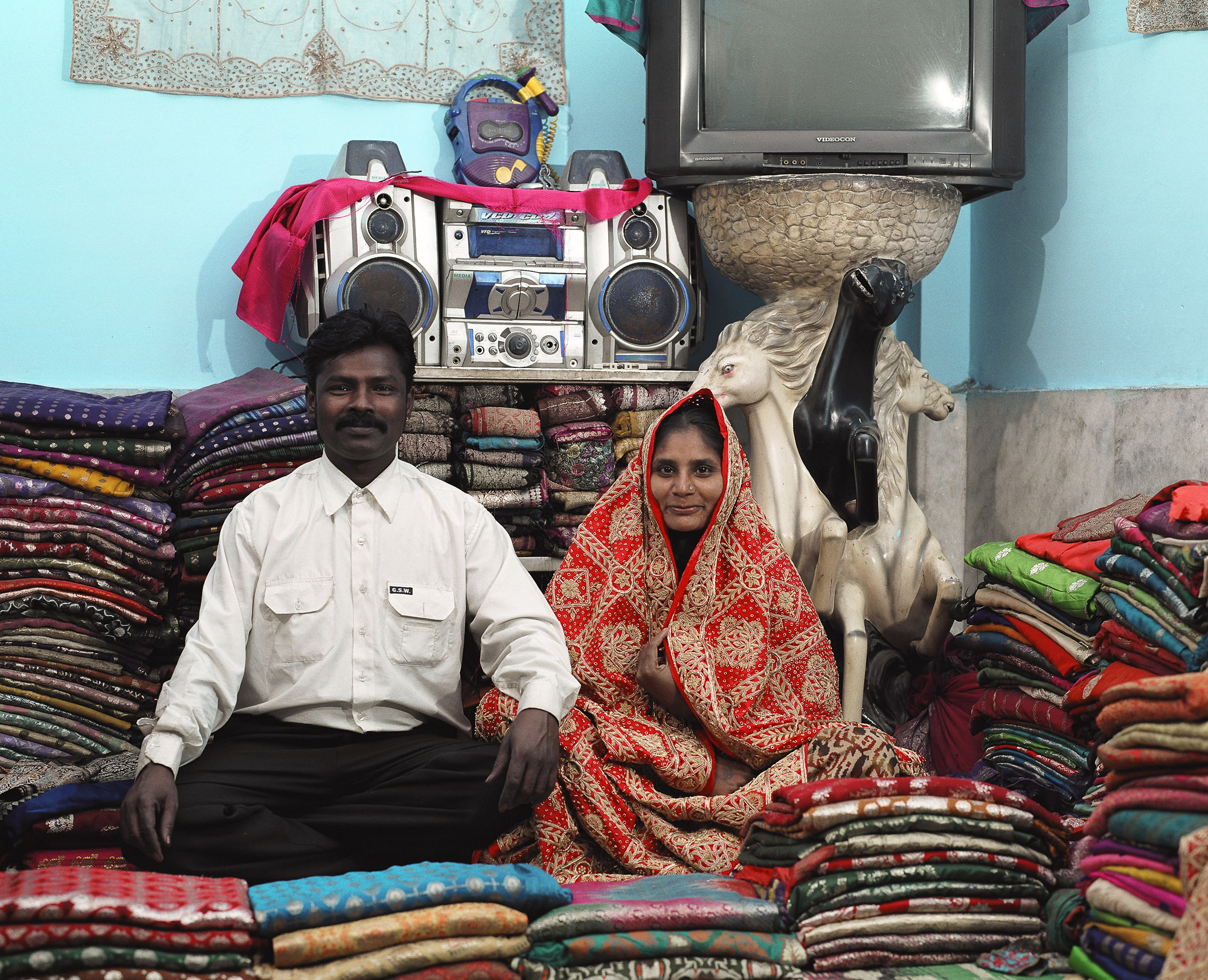 The higher quality clothing will be sold further afield. This Waghri couple deal in silk saris in their home. Such traders amass hundreds of silk saris cast out from wedding trousseau into the secondhand markets for re-sale.