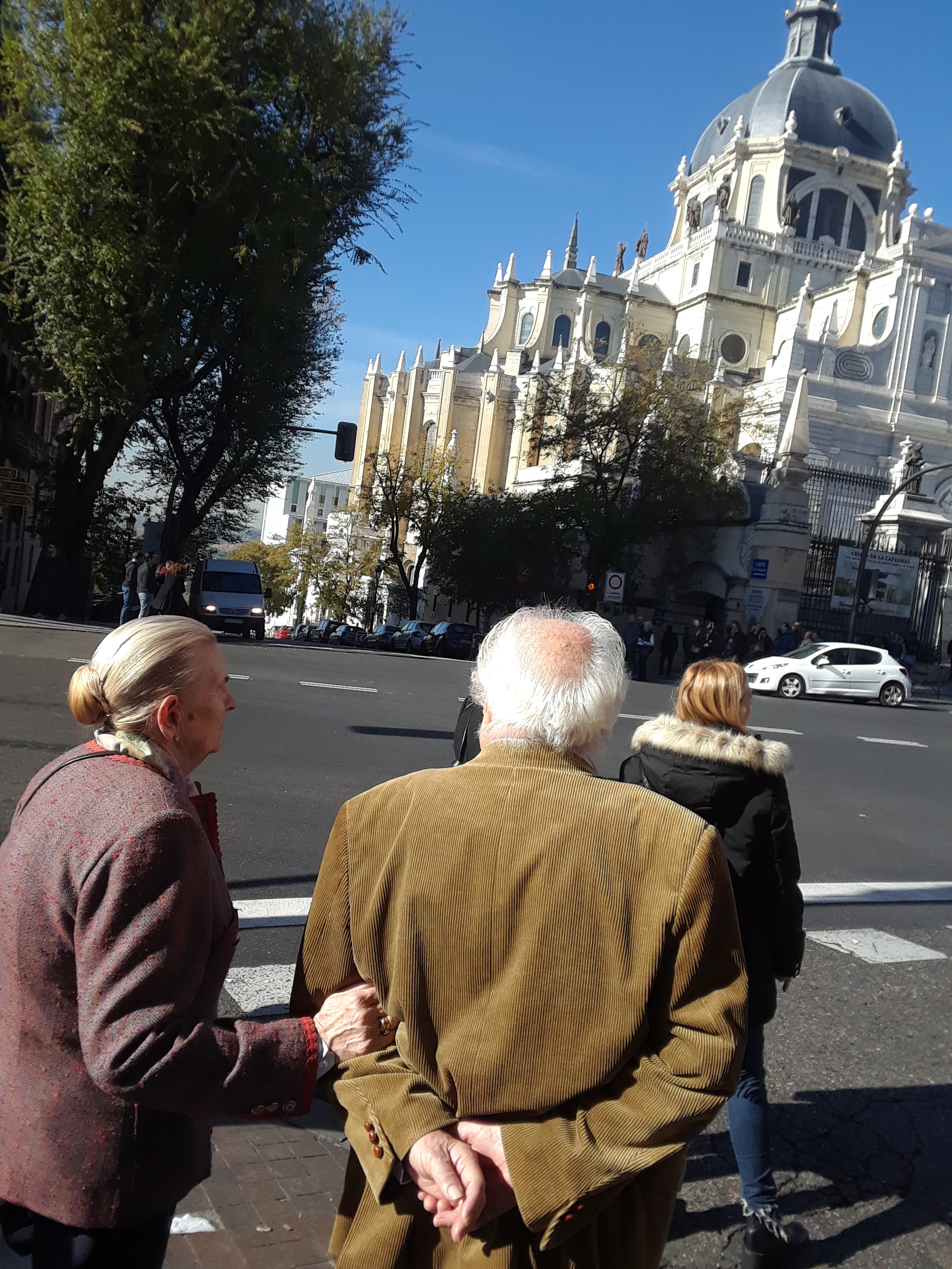 An older couple passes the long-incomplete church.