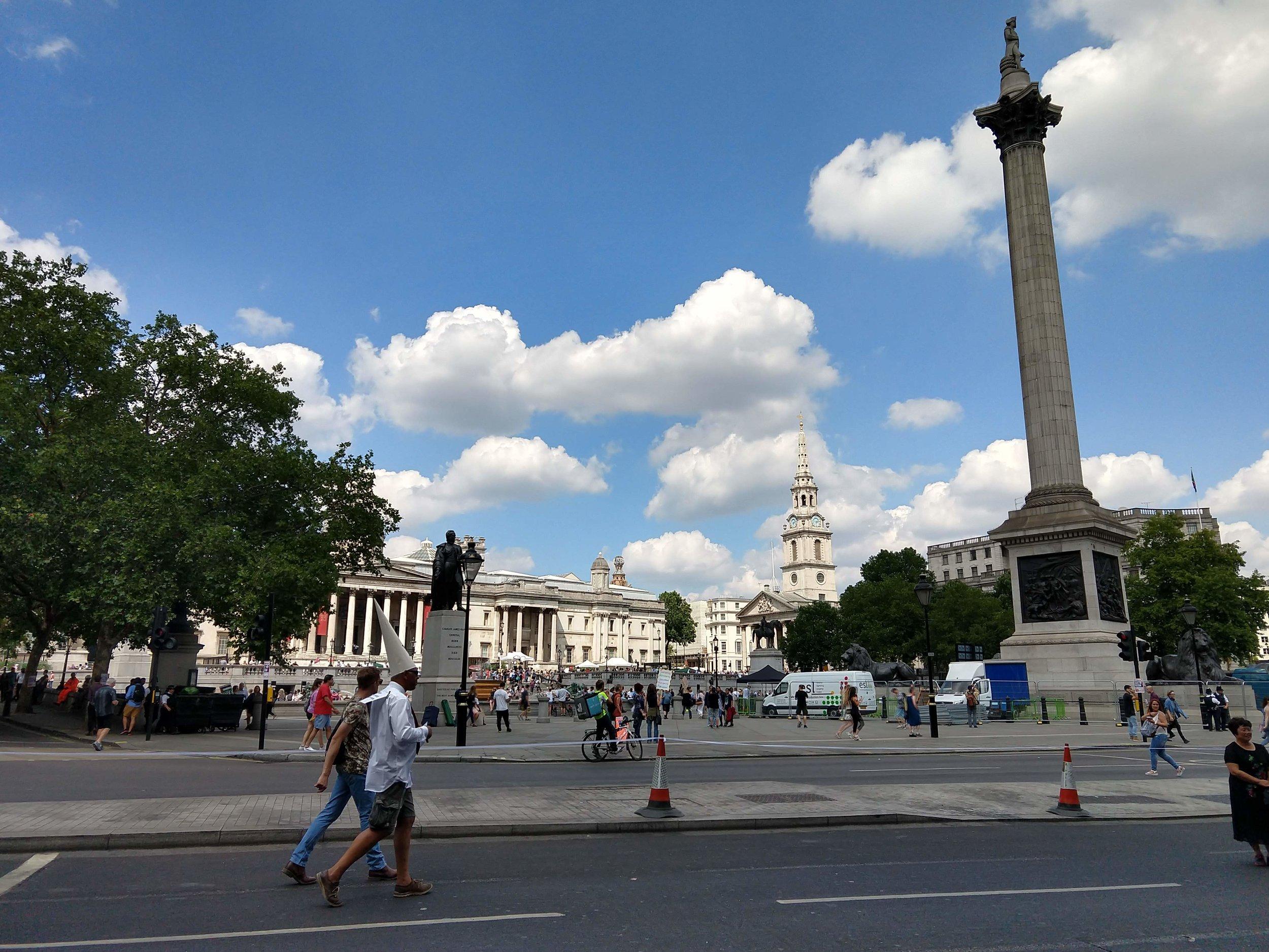 A man in a dunce cap walks past Trafalgar Square.
