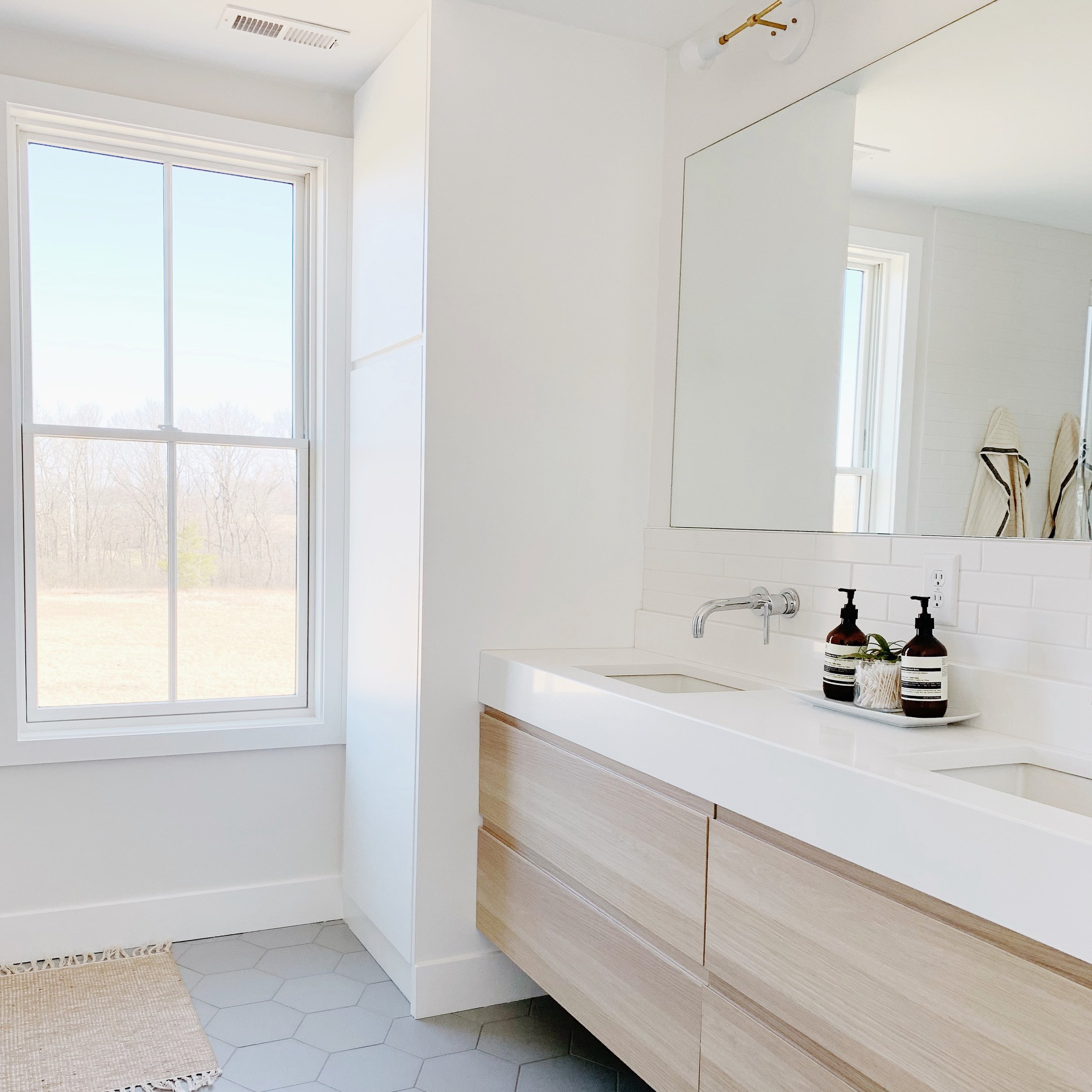 m a s t e r b a t h - An oversized window was the jumping off point for this light and bright space. Featuring IKEA vanities with a custom quartz countertop and under mount sinks, this room proves that a little imagination and hard work makes anything possible.