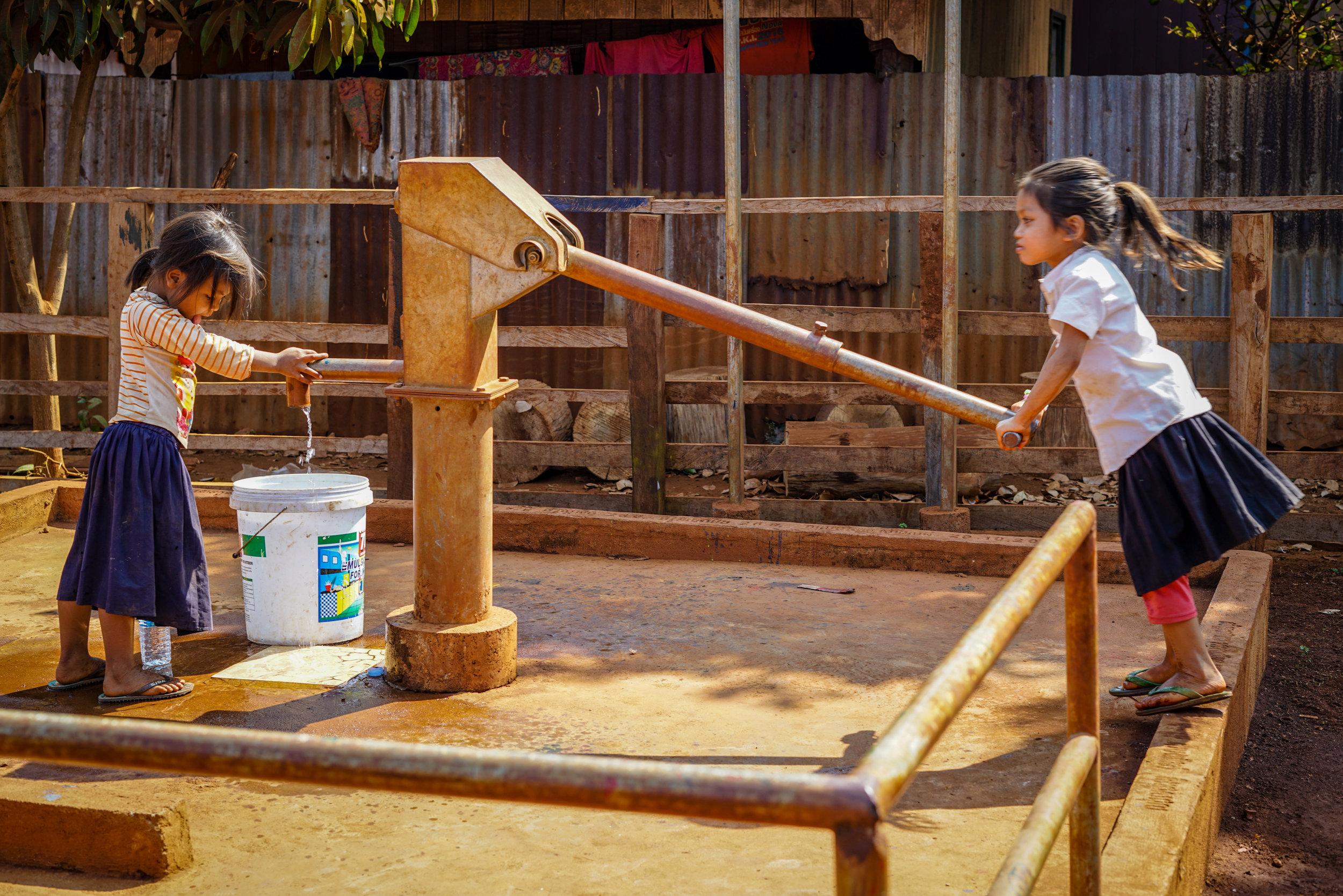 Two girls pump a well | Cambodia   ©LaurenKanaChan
