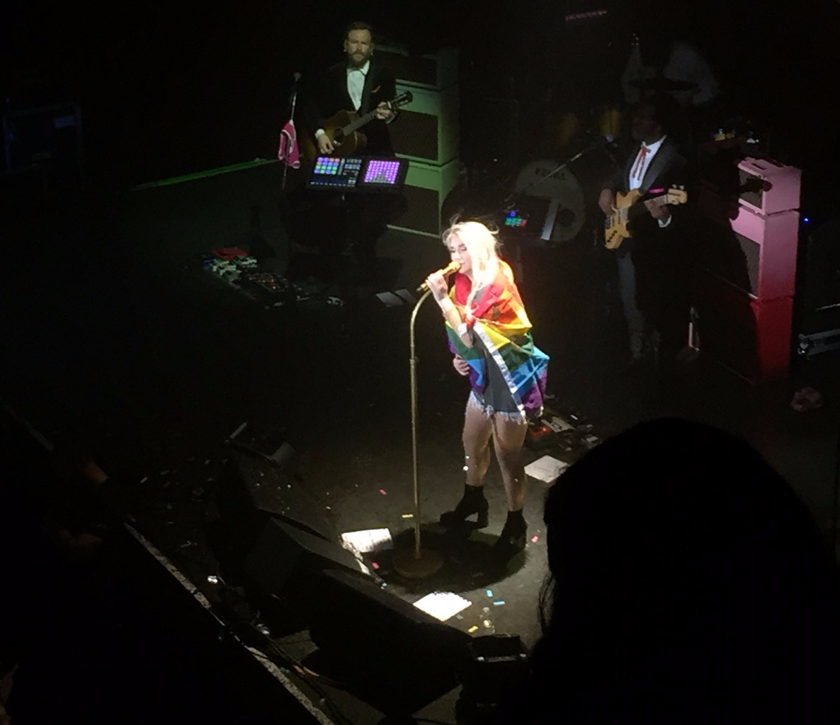 Kesha in a sparkly rainbow flag given to her by fans