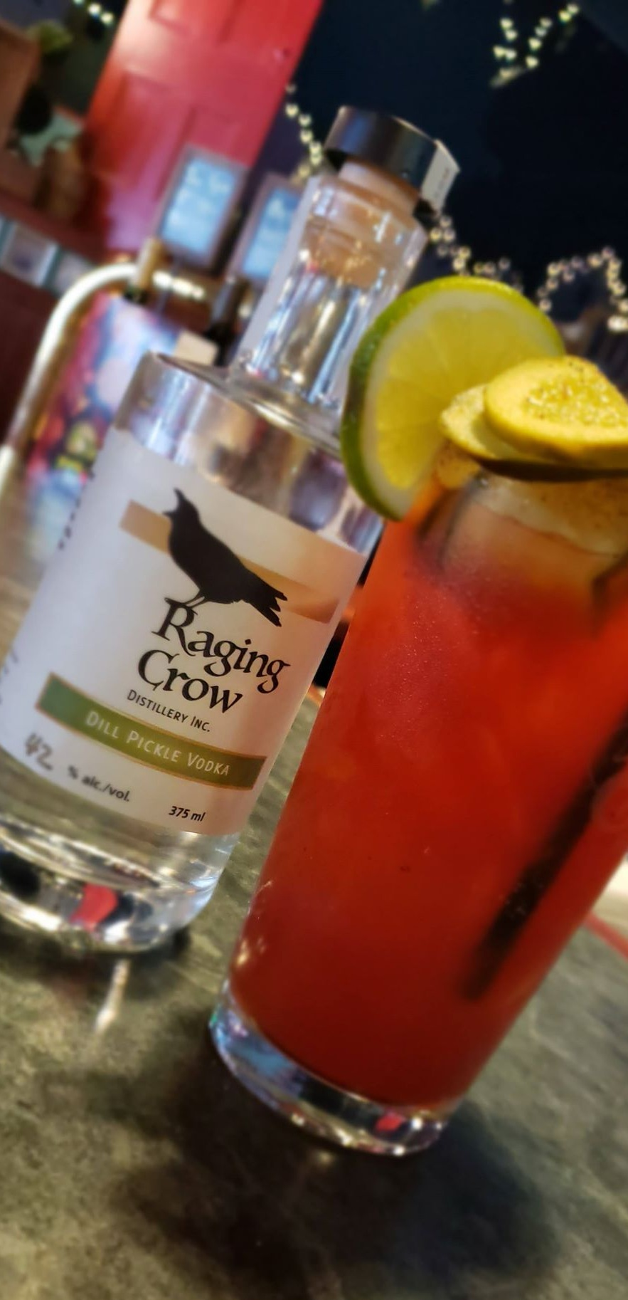 Dill Pickle Caesar - - 1oz Raging Crow Dill Pickle Vodka- 1oz Dill Pickle juice (straight from the bottle)- Tabsaco- Worcestershire- Clamato- Salt & Pepper- Garnished with candied bacon & lime wheel