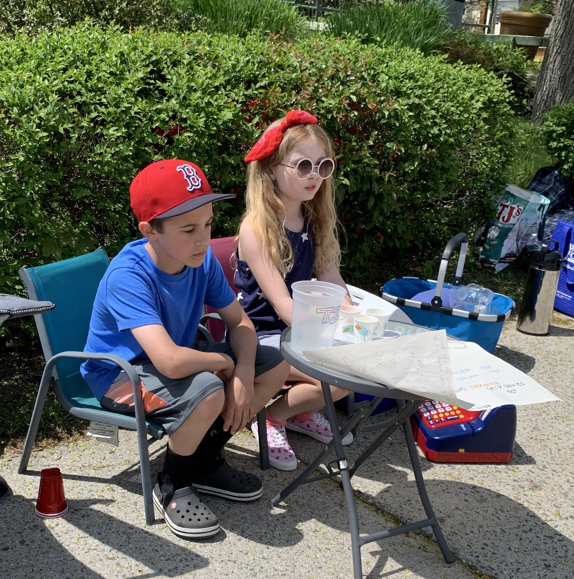 Liam and his friend set up the perfect spot for their lemonade stand at the Memorial Day parade