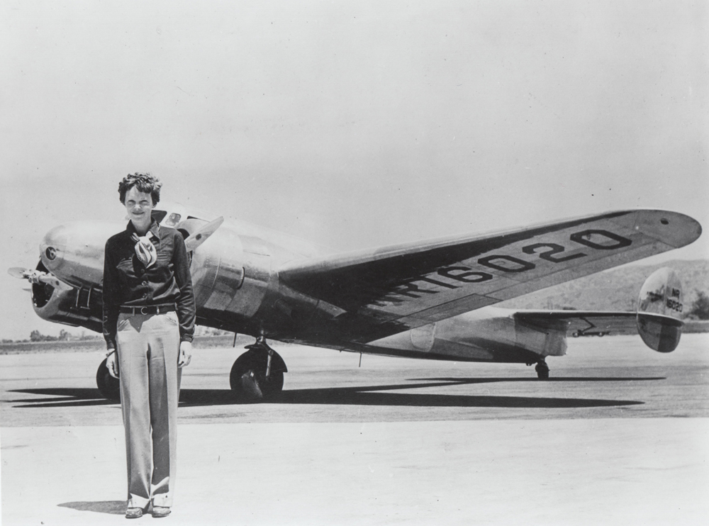 Amelia Earhart standing with the last plane she ever flew: her Lockheed Electra.  International Women's Air and Space Museum