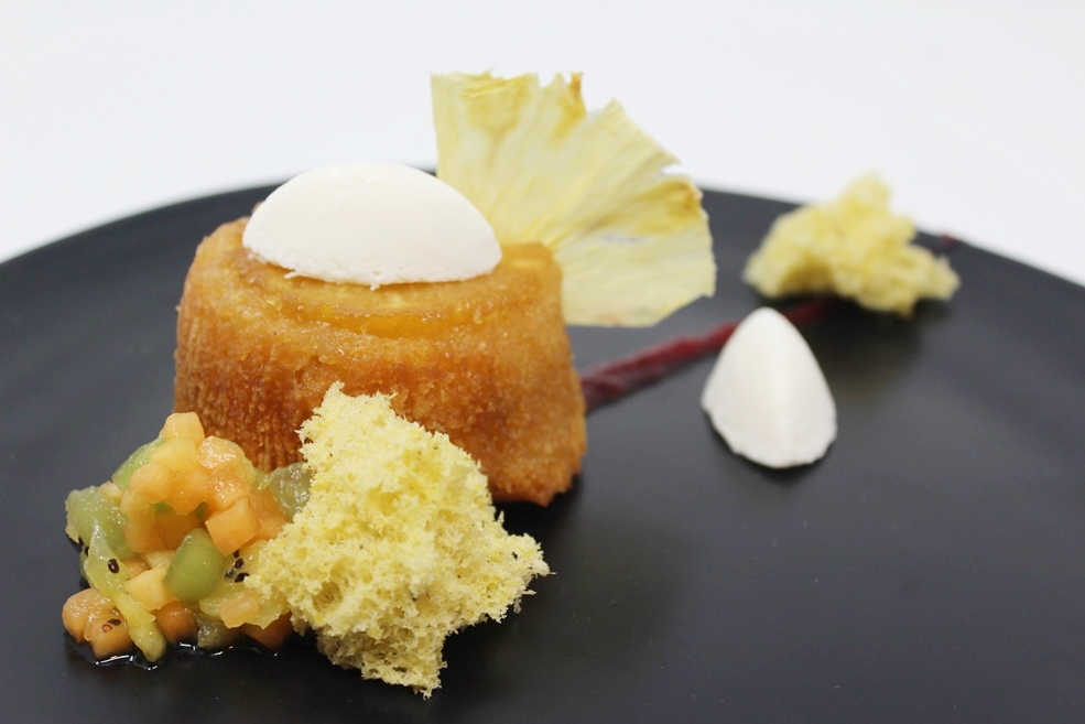 Ziegfeld Ballroom's Deconstructed Upside Down Pineapple Cake with Coconut Cream Mousse, Pistachio Sponge, and Tropical Fruit Salsa.