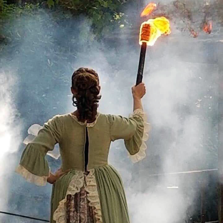 A member of the cast of Horn in the West holds the torch.