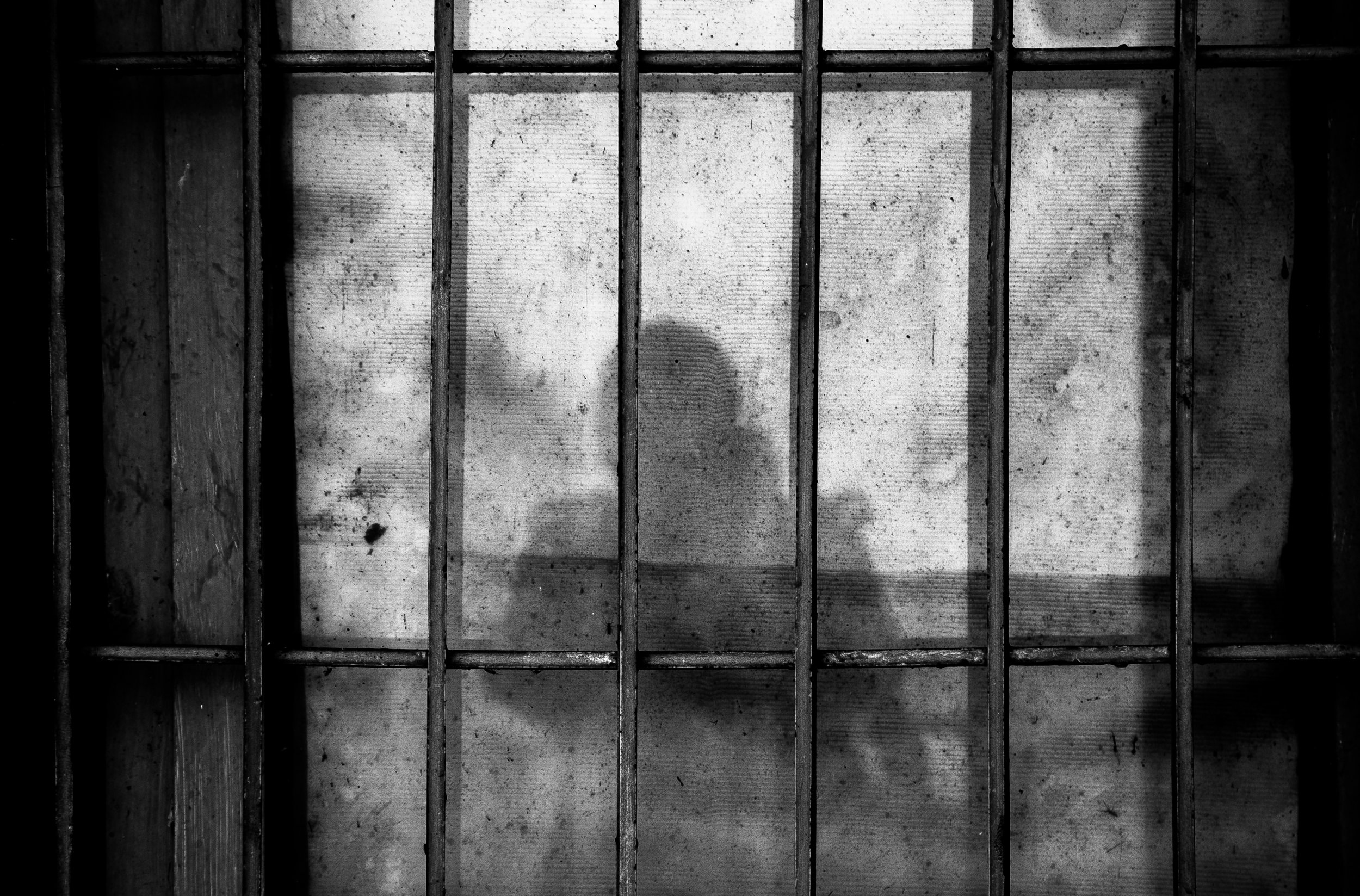 Image of a shadow and a jail cell. Credit: Ye Jinghan/Unsplash
