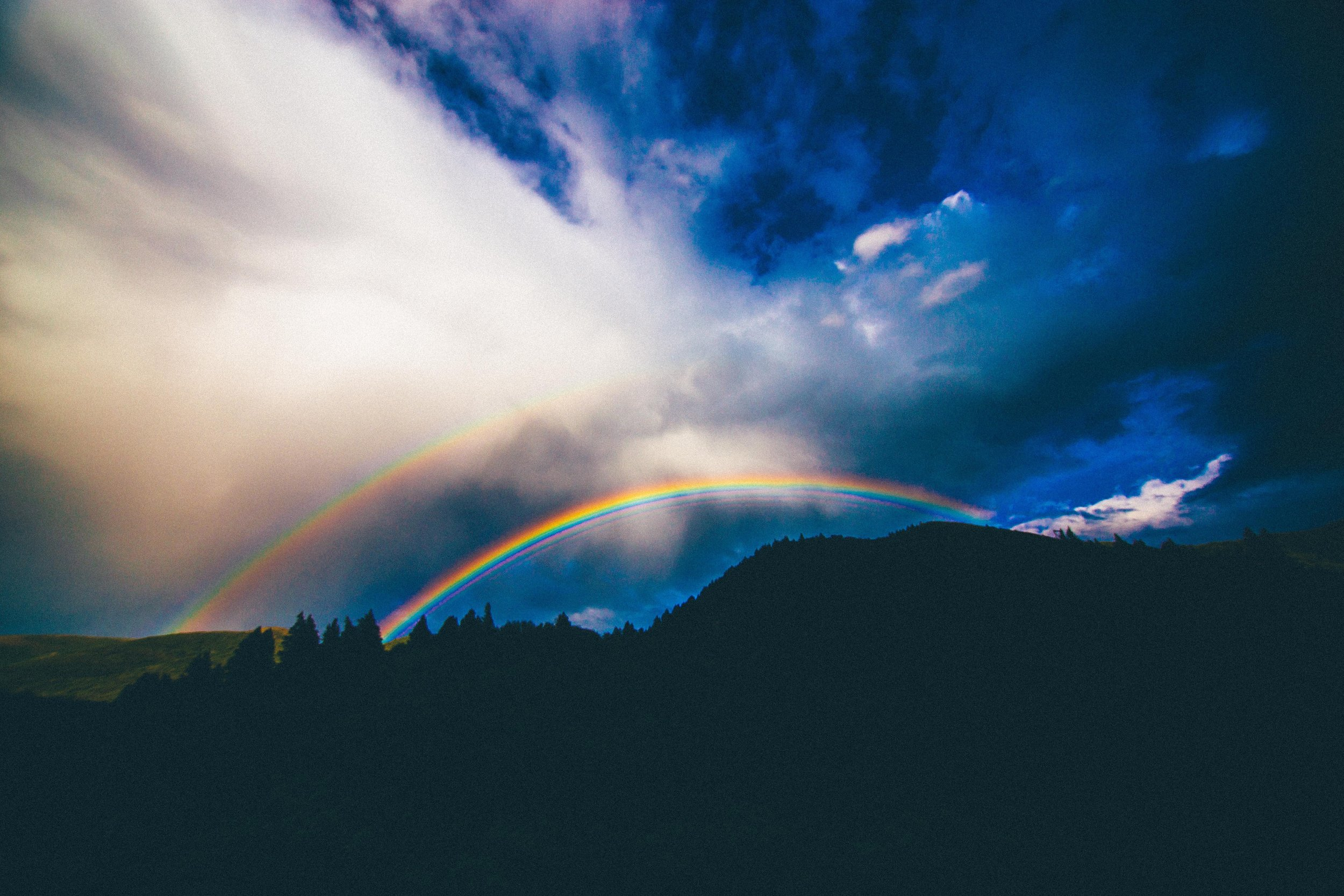 A rainbow appears over a forest and hills. Credit: Abigail Keenan/Unsplash