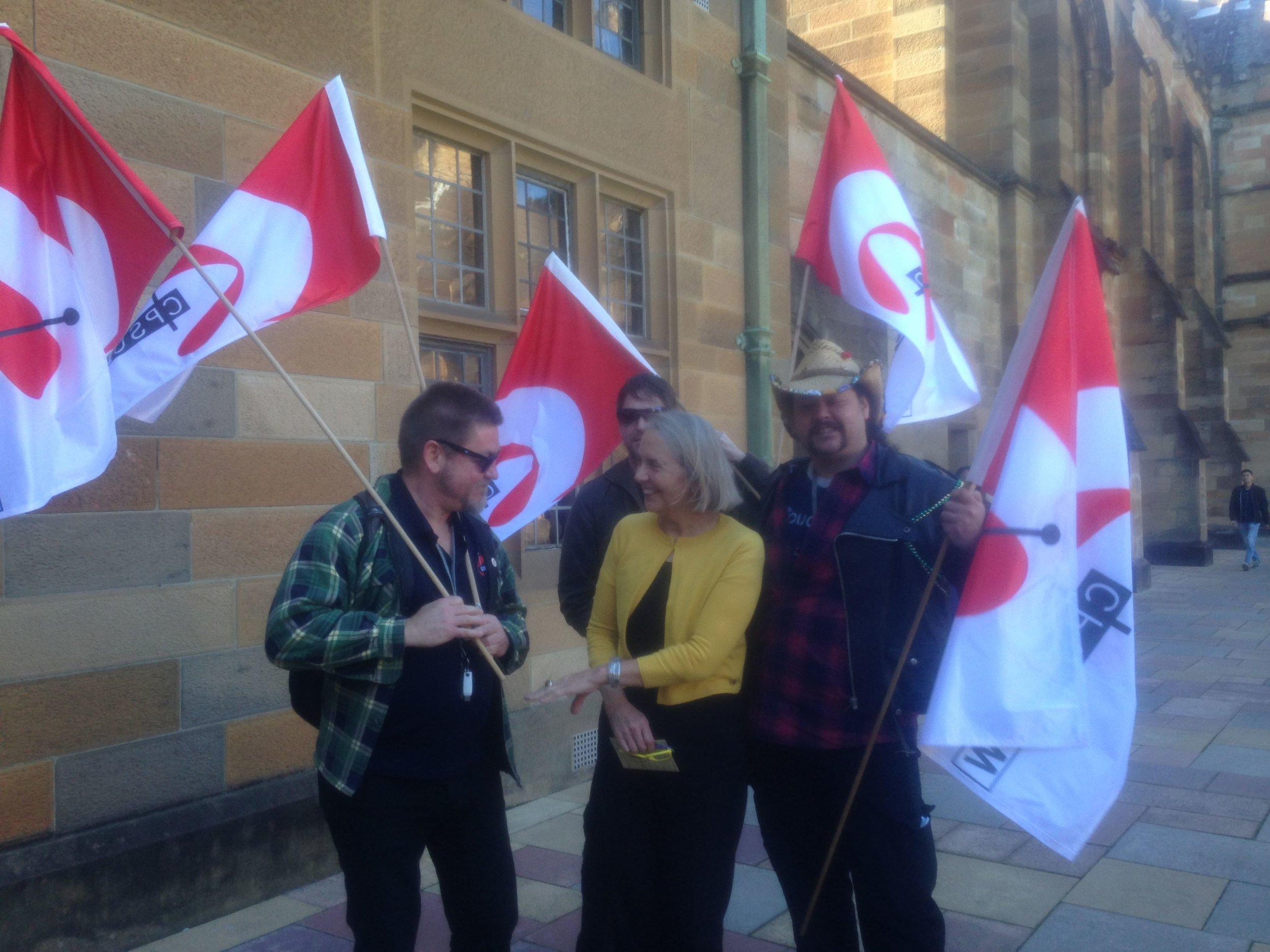 Senator Lee Rhiannon, an alumni of UNSW, surrounded by flag-bearing supporters outside Vice-Chancellor Michael Spence's office in the Quadrangle of the University of Sydney