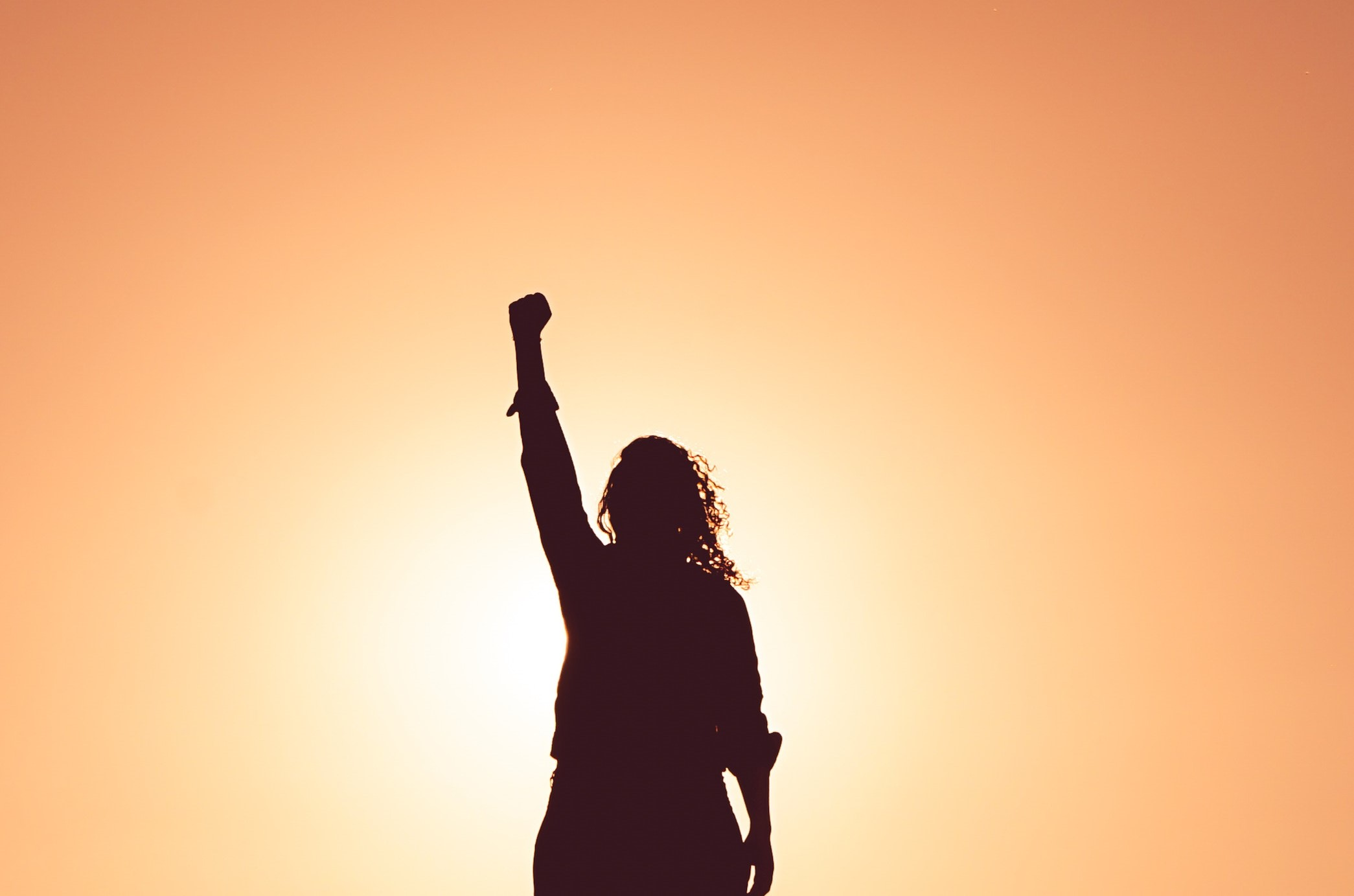 Woman in shadow with her fist raised in the air