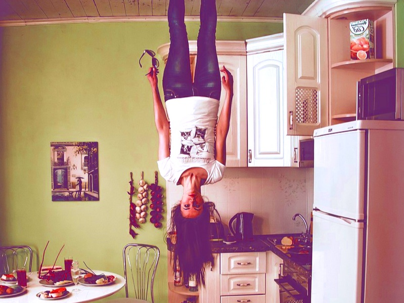 Woman holding sunglasses standing upside down on ceiling in kitchen next to white refrigerator
