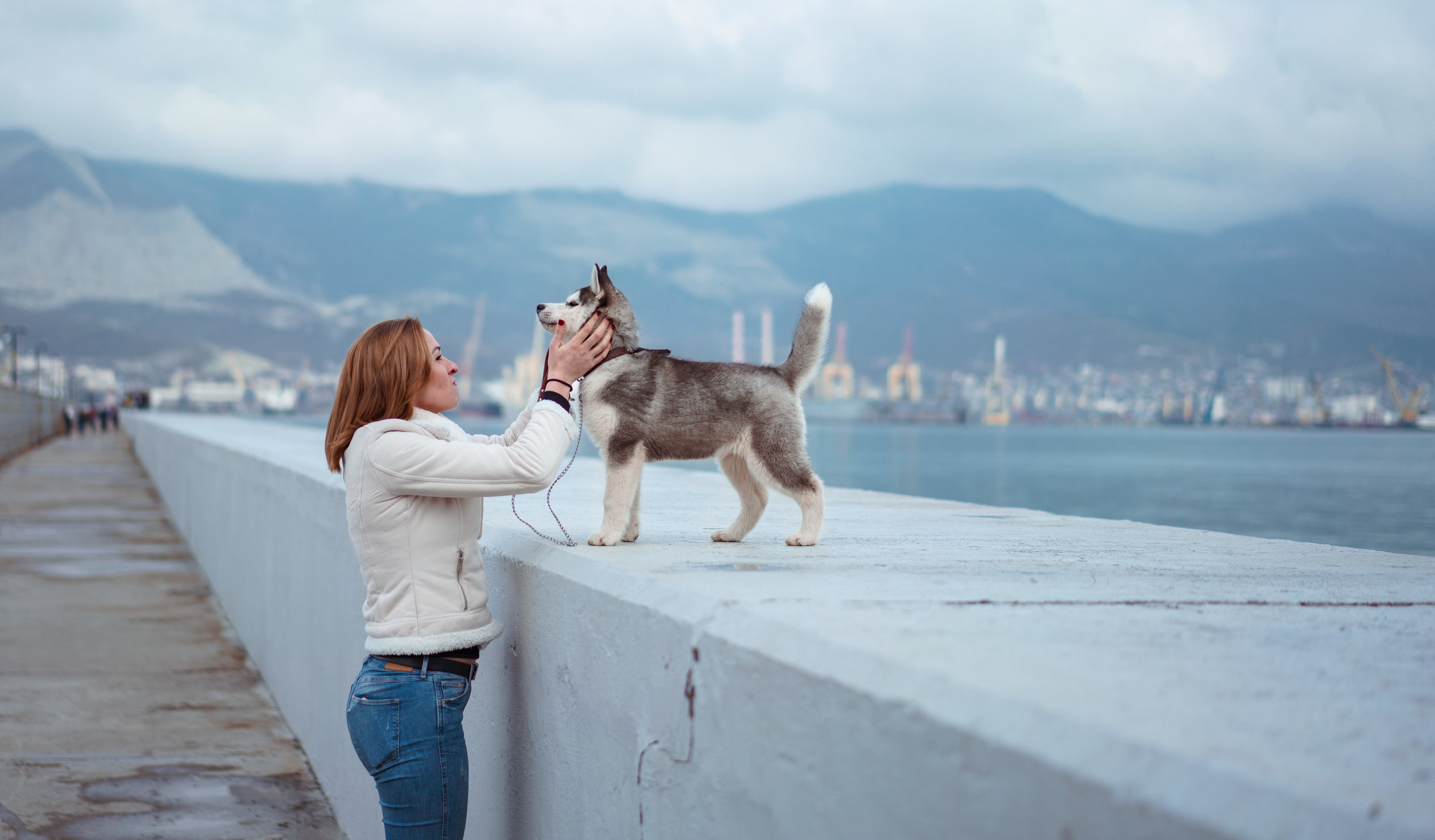 Woman petting puppy while standing next to a bay