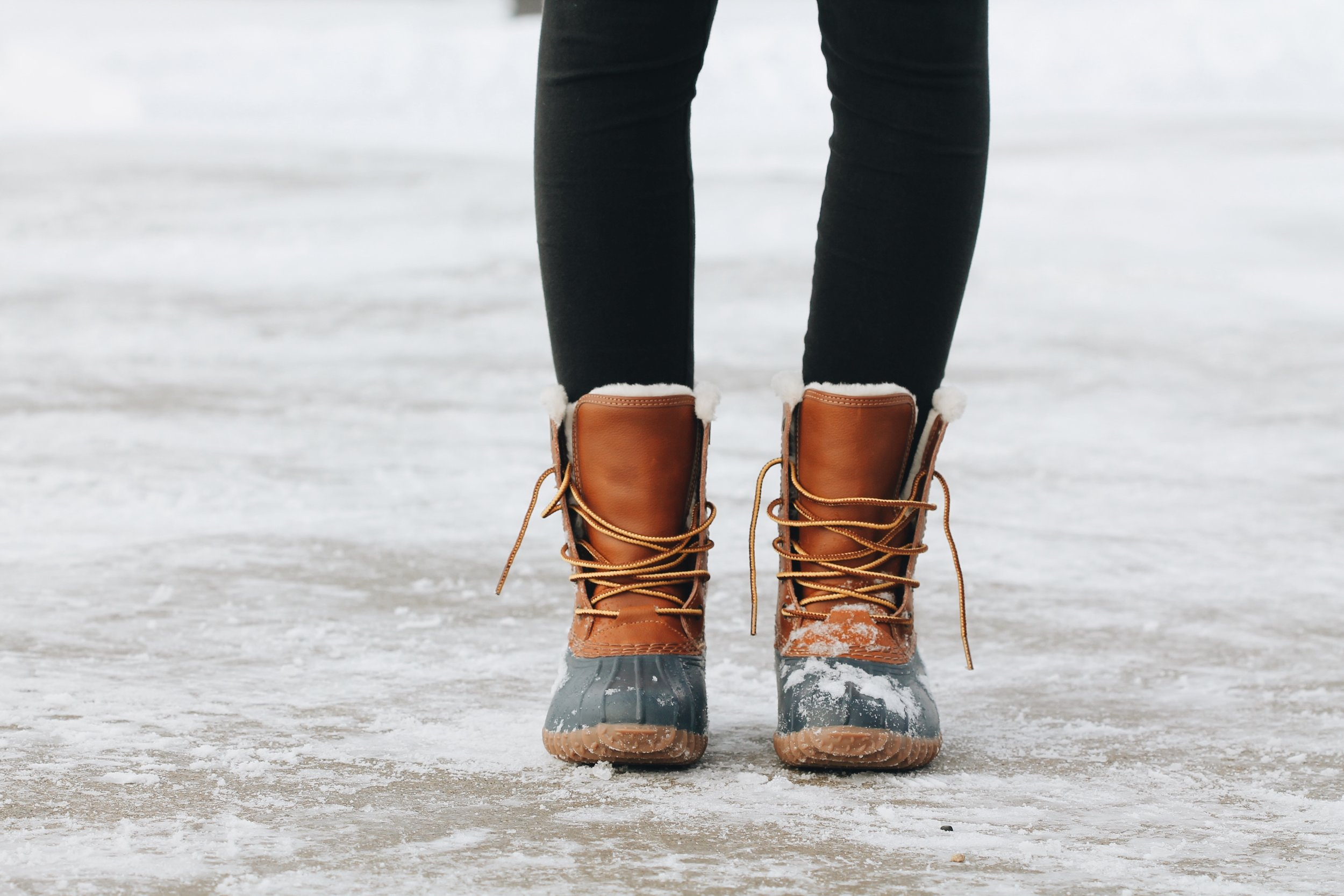 Legs of female wearing snow-covered snow boots standing on icy sidewalk
