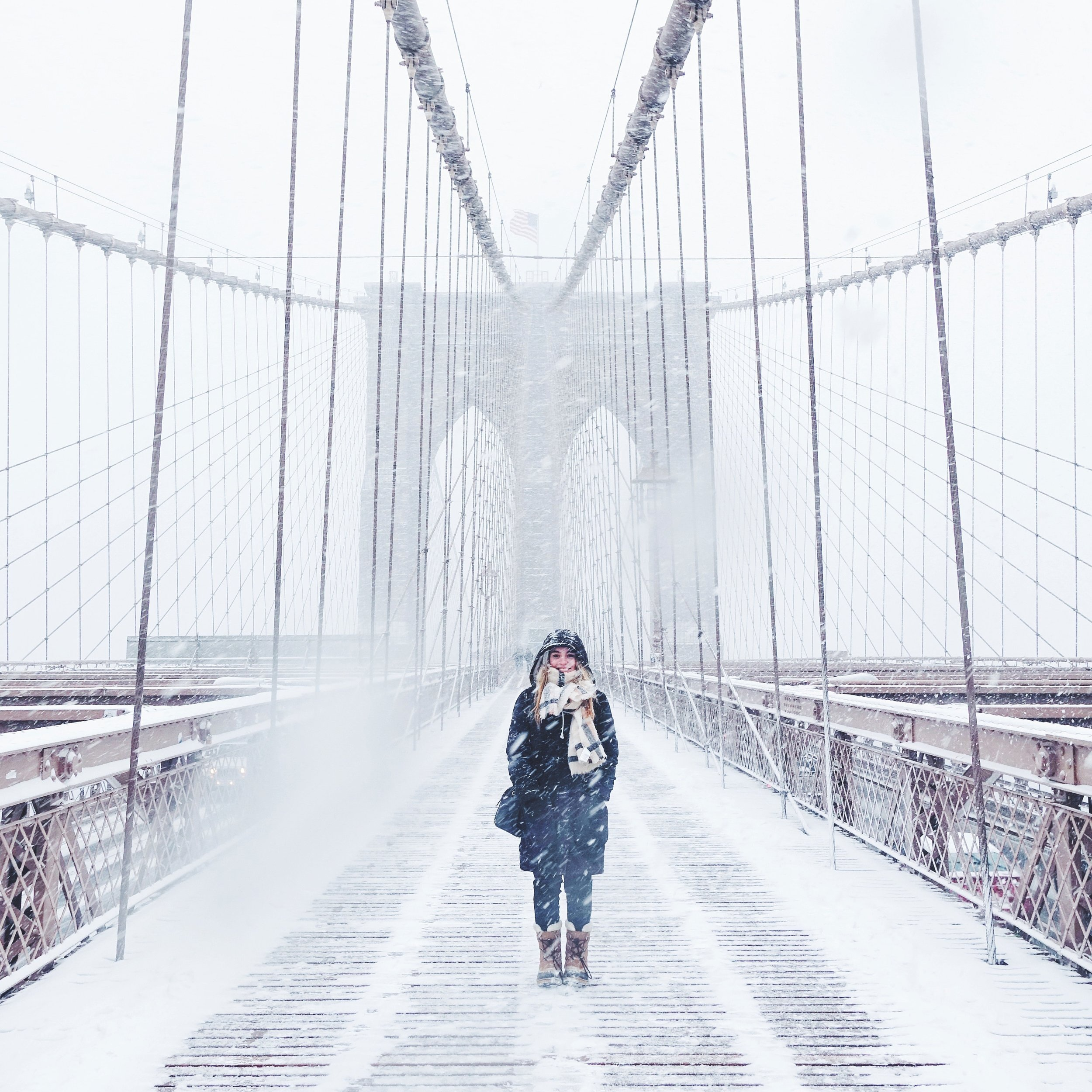 female+standing+on+bridge+with+heavy+coat+and+boots+as+snow+falls+around+her