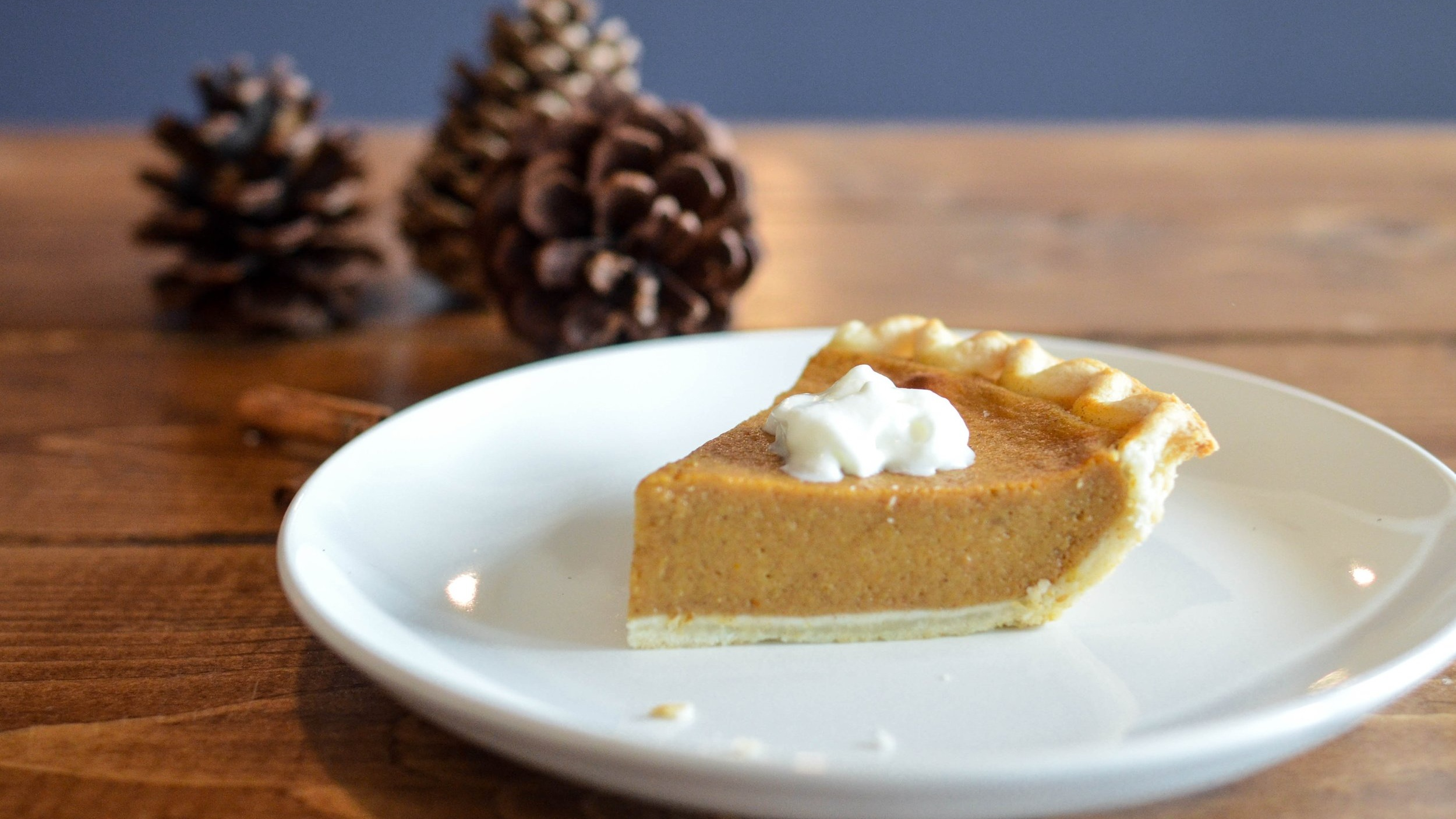 Acorns next to White plate with slice of pumpkin pie on wooden table