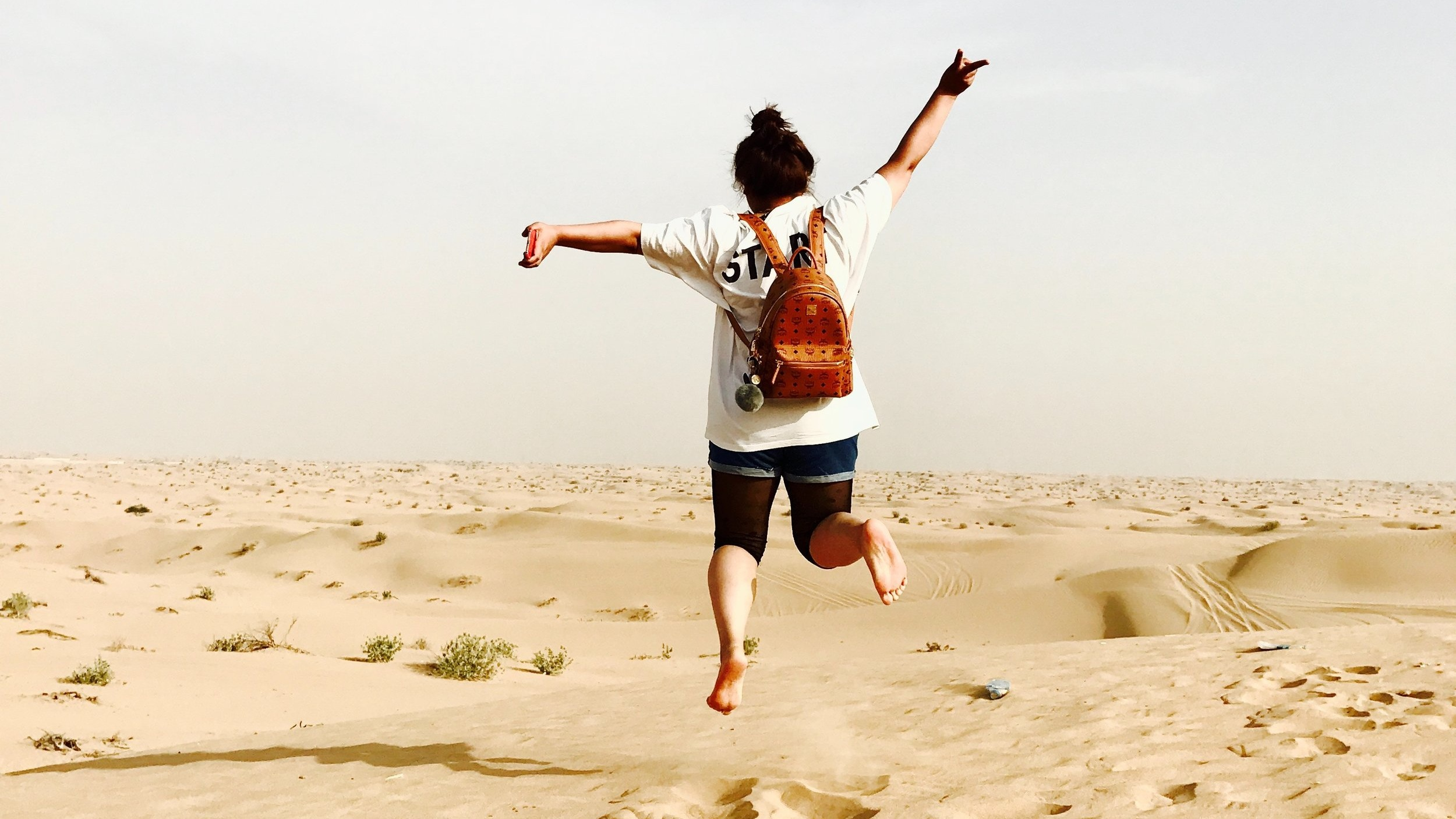 woman wearing backpack facing away jumping up in the desert sand