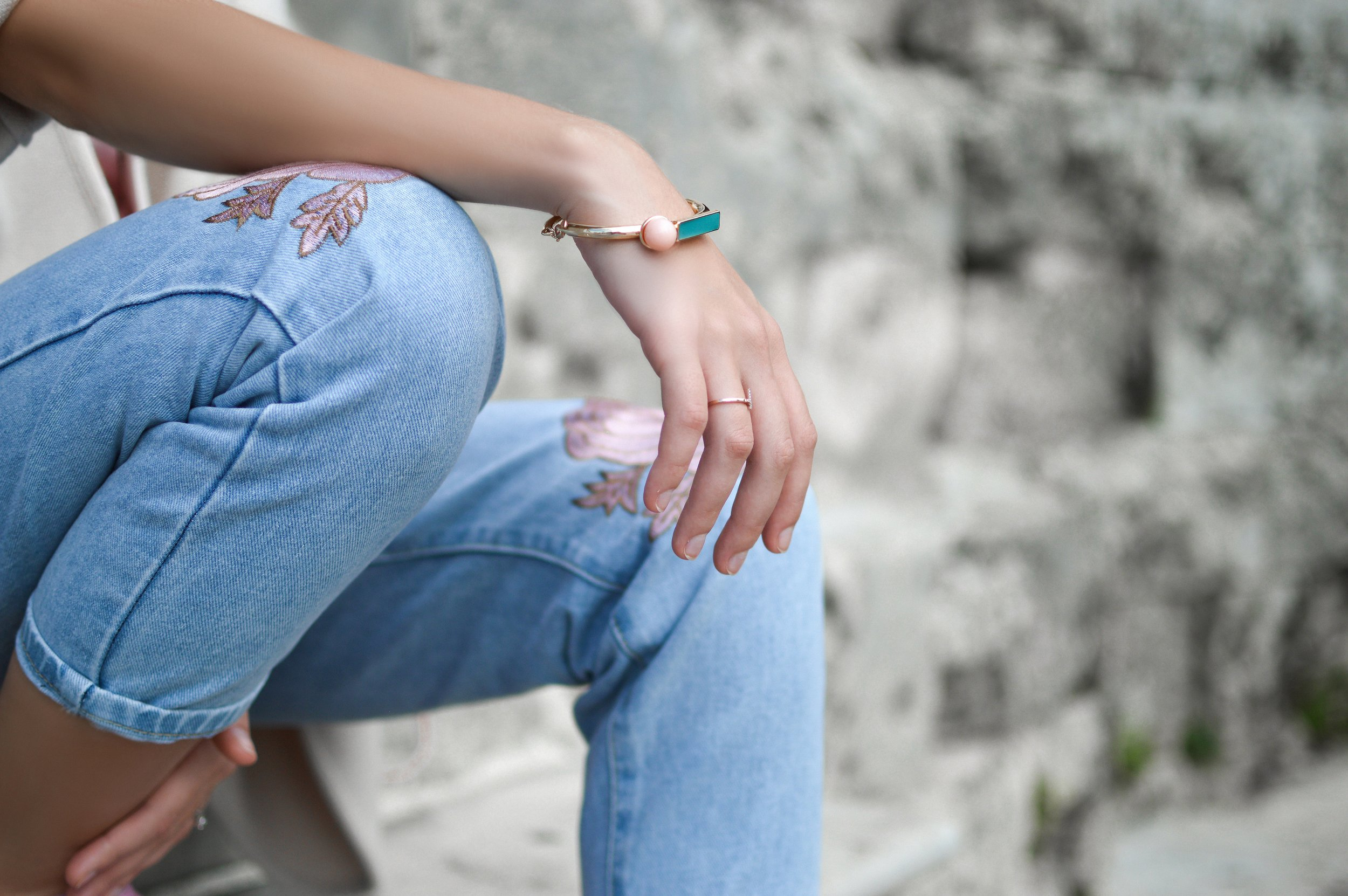 woman sitting down, resting her arm on her knee, and wearing embroidered blue jeans and a gold and turquoise bracelet