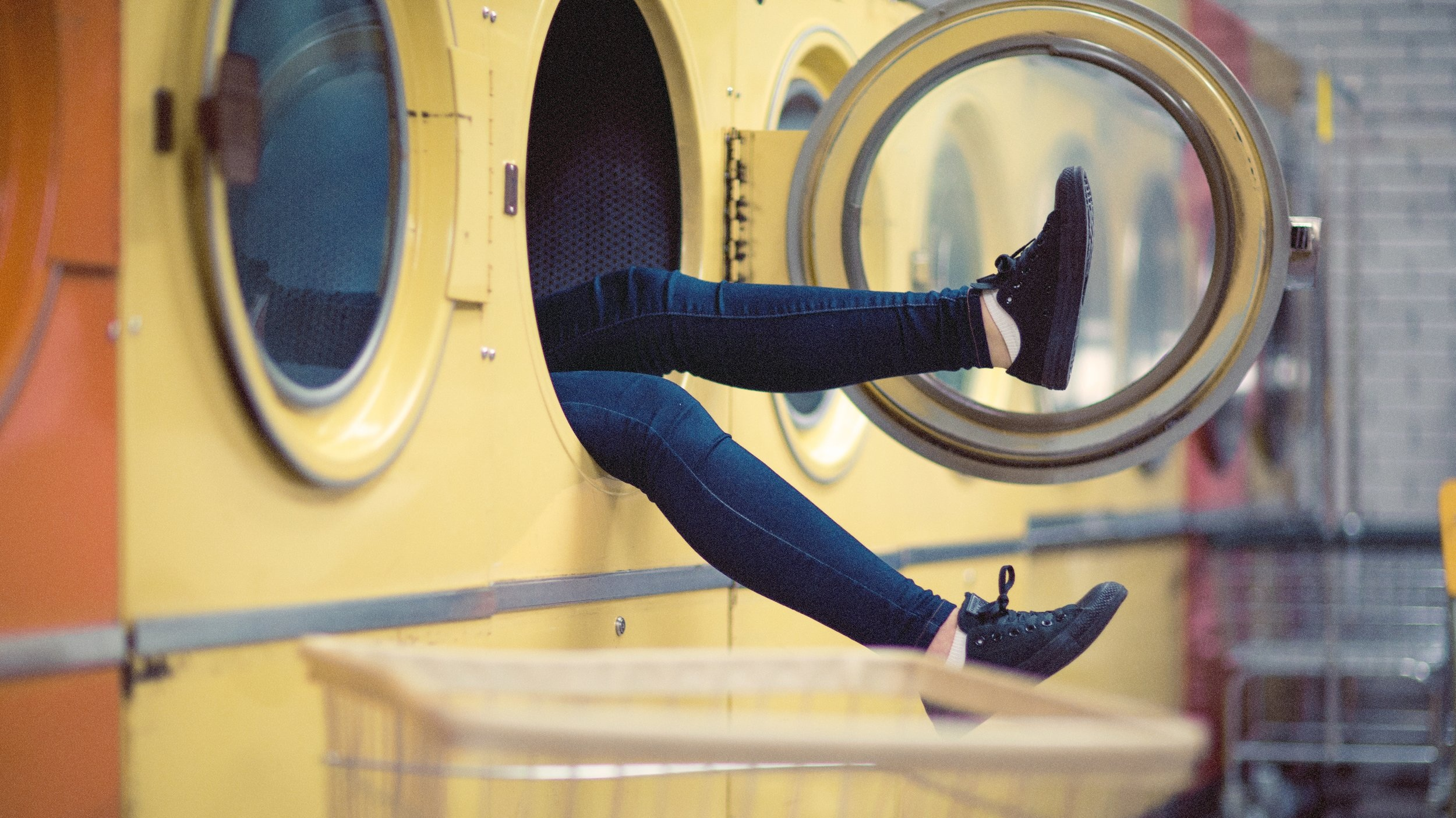 woman inside large yellow dryer with the door open and legs hanging out of