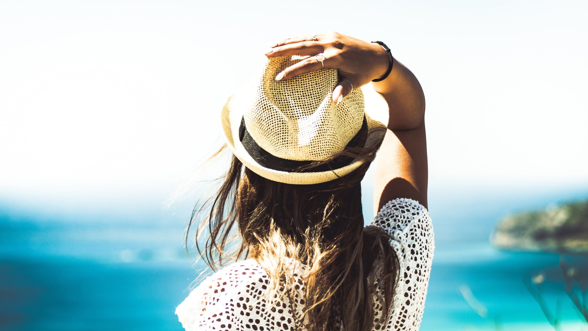 woman holding hat on head looking out to blue ocean