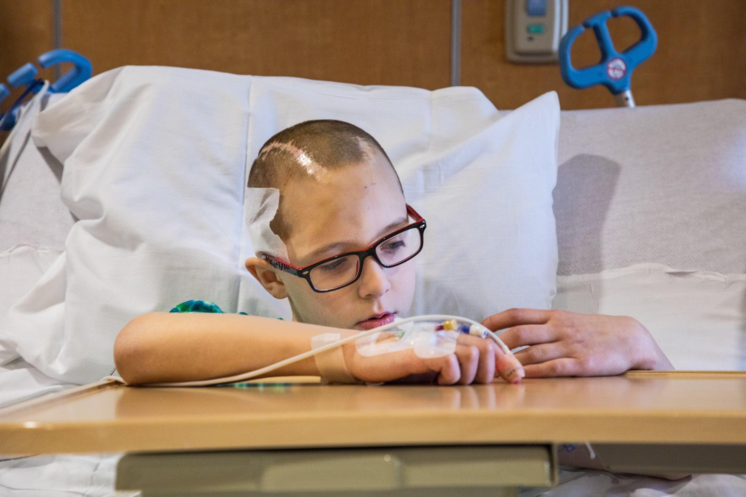 Christian looks at his hands while sitting in his hospital bed Feb. 25, 2019, after doctors removed a small tumor protruding on the right side of his head. This was Christian's fifth brain surgery in two years.