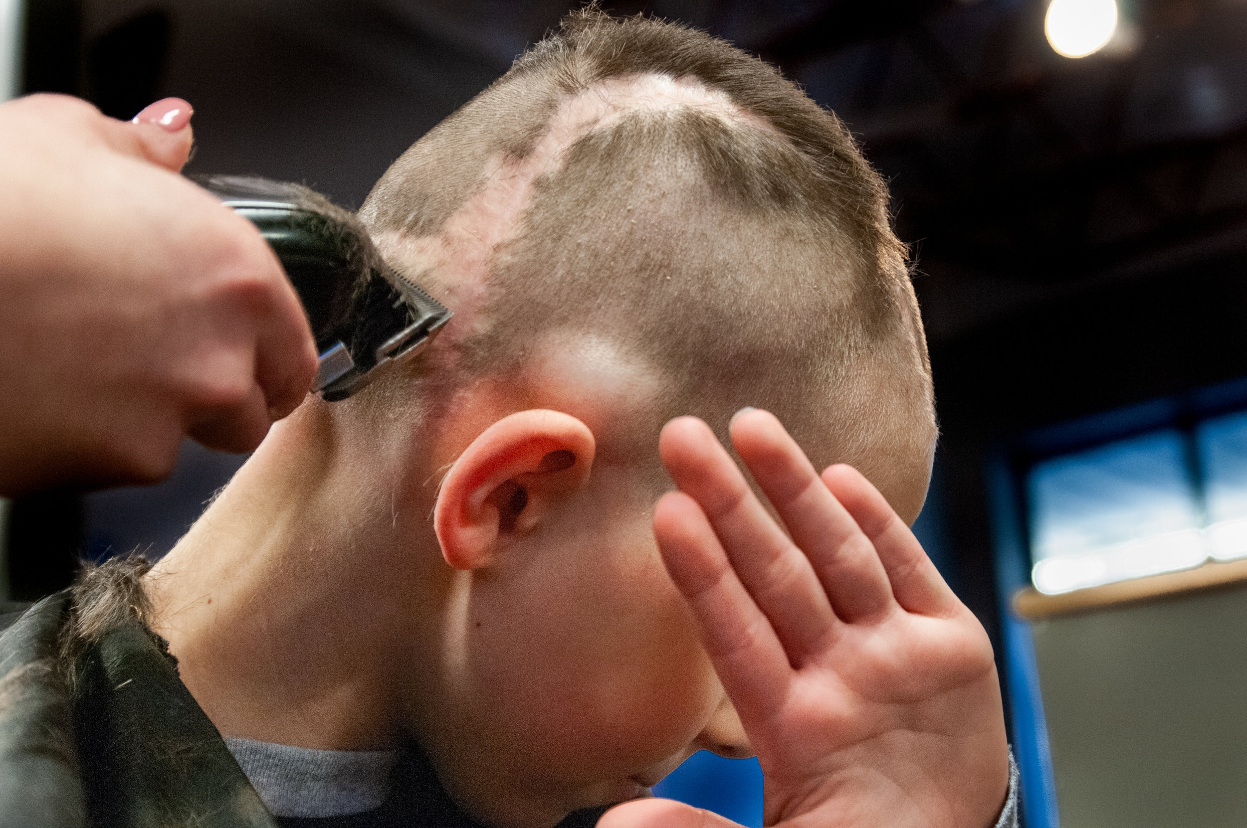Christian hides his face from both the camera and falling hair during a haircut prior to his fifth brain surgery in Feb. 2019. The bump above his right ear is a tumor doctors will remove during surgery to test further against medications and to alleviate Christian's head pain and aches.  | PHOTO BY   MADELINE GROSH