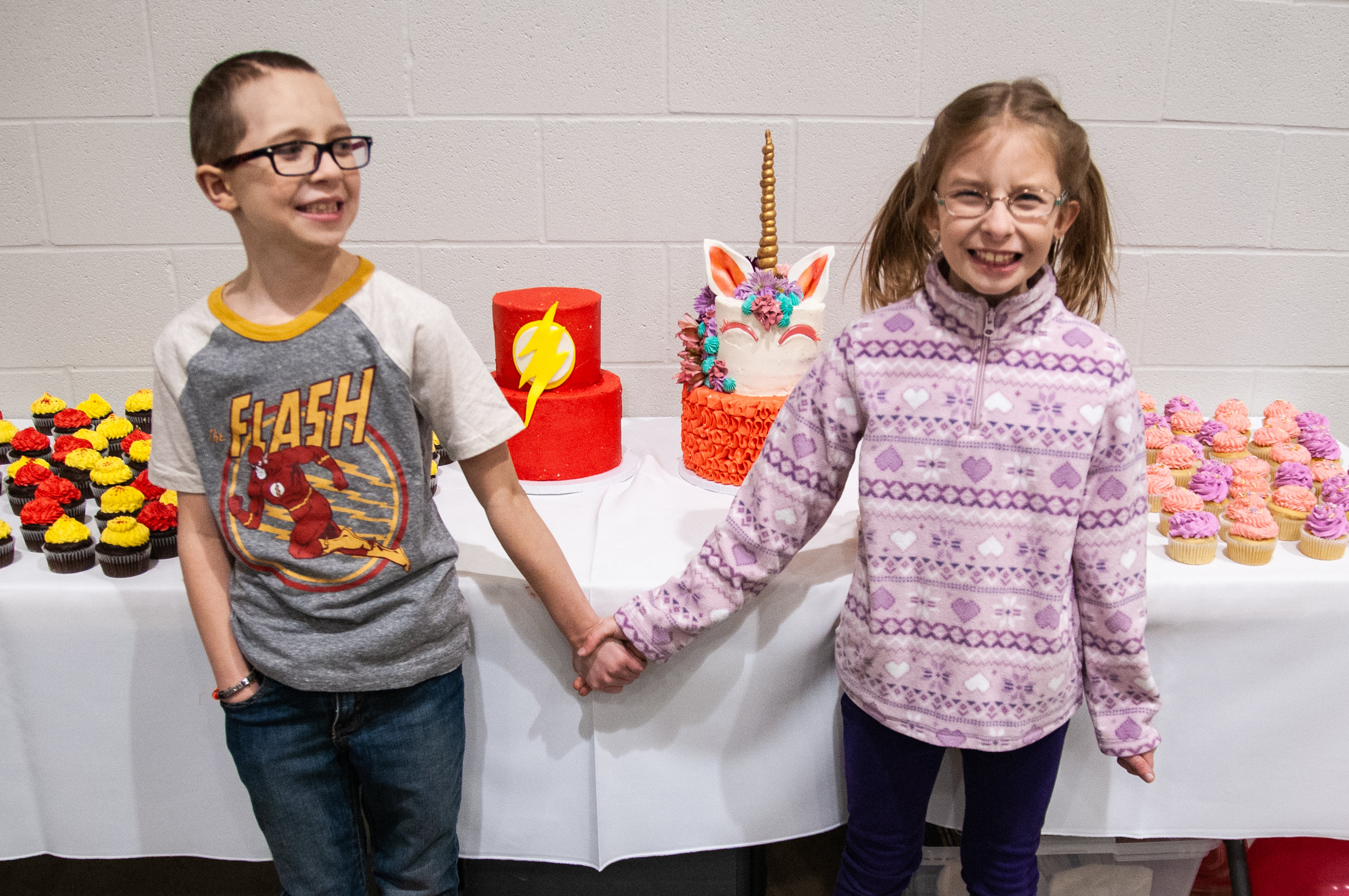Christian and his twin sister, Grace, hold hands before cutting their cakes at the 8th Birthday Bash in Muncie, Ind. All decorations, food, activities and games were donated by community members to help celebrate the twins' birthday.  | PHOTO BY   MADELINE GROSH