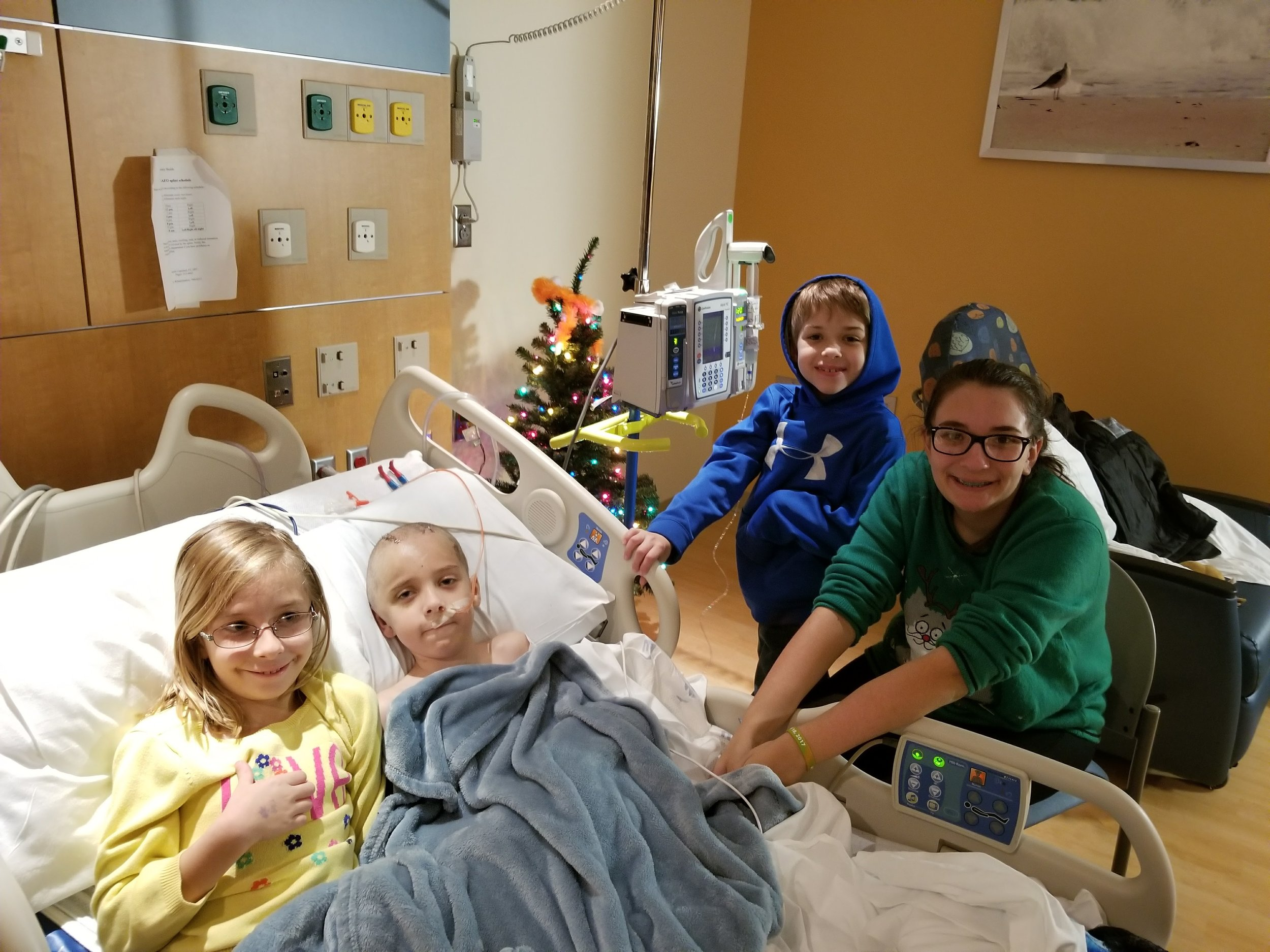 (left to right) Grace, 6, Christian, 6, Eli, 8, Madyson, 13, pose for a photo in Christian's hospital room at Riley Hospital for Children Nov. 30, 2017, just over a month after Christian was first admitted to the hospital. The siblings were not able to visit Christian often due to flu restrictions and the severity of his care. Christian would cry and beg his siblings not to leave at the end of the day.  | PHOTO COURTESY OF DAUGHERTY FAMILY