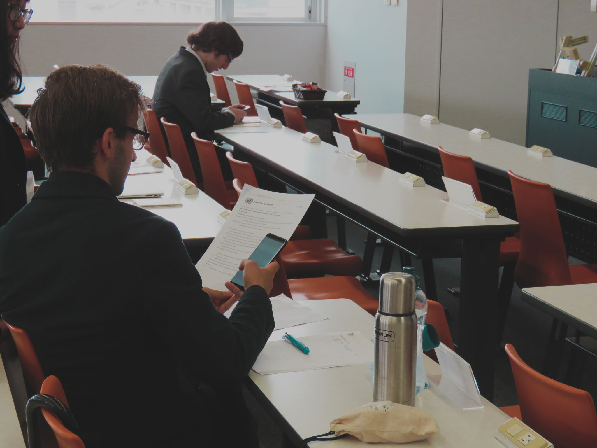Arriving early at the venue, the delegate of Germany goes over his documents before Day 2 begins.