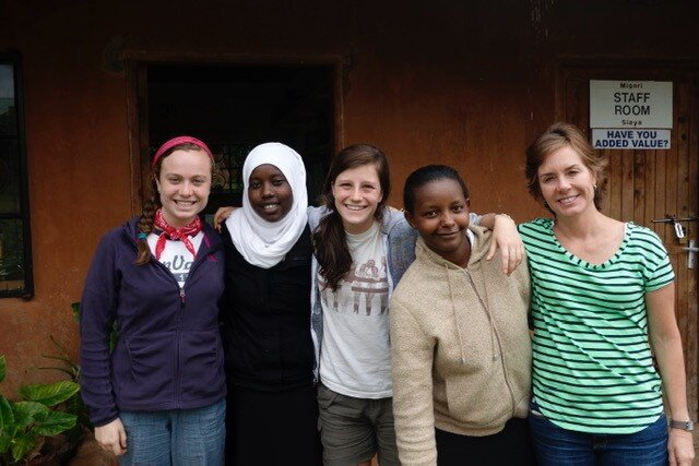Pictured: Carrie (right), and her daughter, Leigh (left), alongside students and volunteers from the Daraja Academy.