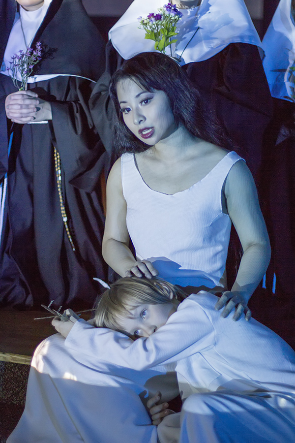 Jacqueline as Angelica in Puccini's  Suor Angelica  at Opera Mariposa  ( 2014). A singing Jacqueline is wearing a white dress and sits on the ground with a small child laying on her lap. She is surrounded by nuns holding flowers. Photograph: Diamond's Edge Photography.