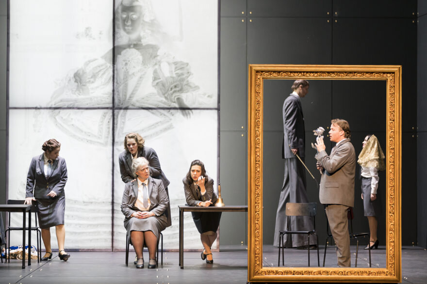 On the right, the Dwarf, the chamberlain (on stilts) and the Infanta stand inside a gold picture frame. To the left, four women in grey suits look on.  Der Zwerg , Oper Graz. Photograph by Werner Kmetitsch (2016).