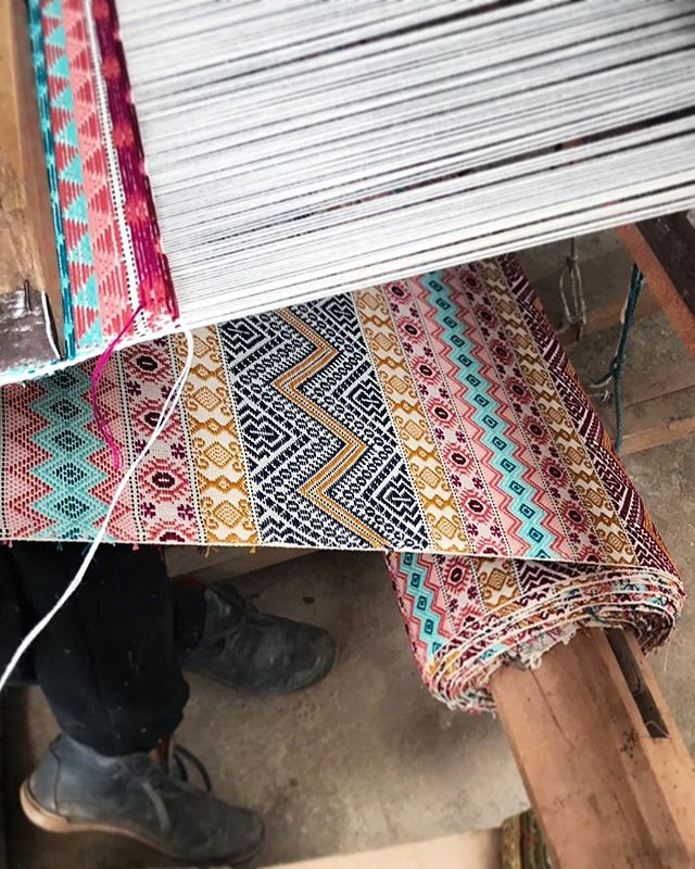 Holmul Falseria fabric on the loom. Hand weaving the Falseria collection is a very physical process - the 29 shafts are selected by hand & lifted by foot & the shuttle is passed by hand.  Only our most skilled master weavers can achieve the complex pattern & many colours of the Holmul design. And we salute them! 🙌