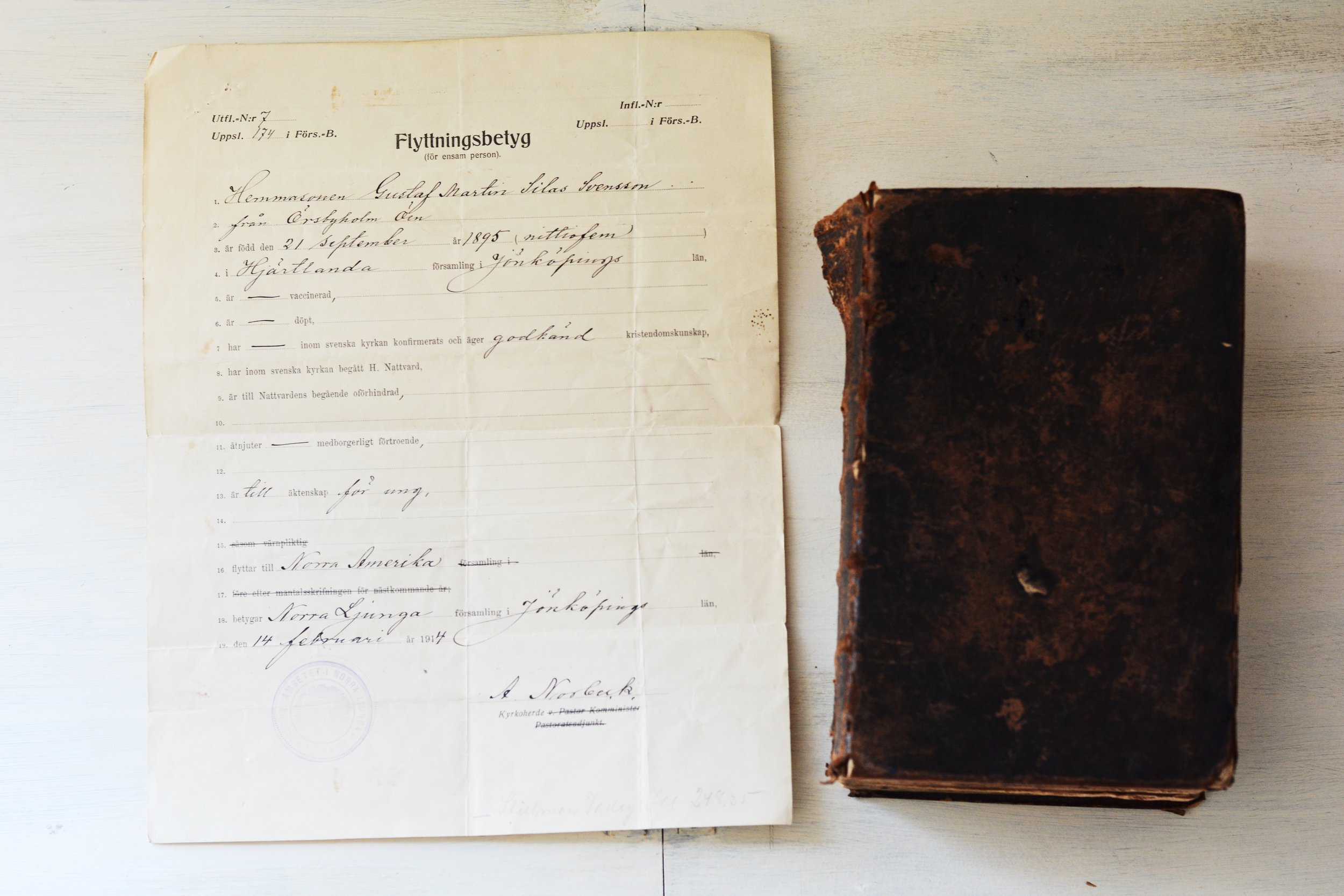 My great-grandfather's 1) Flyttningsbetyg or, official exit permit, issued by the pastor of the parish in Sweden from which he resided so that he could come to America as an immigrant, and 2) Bible brought over to America from the old country.