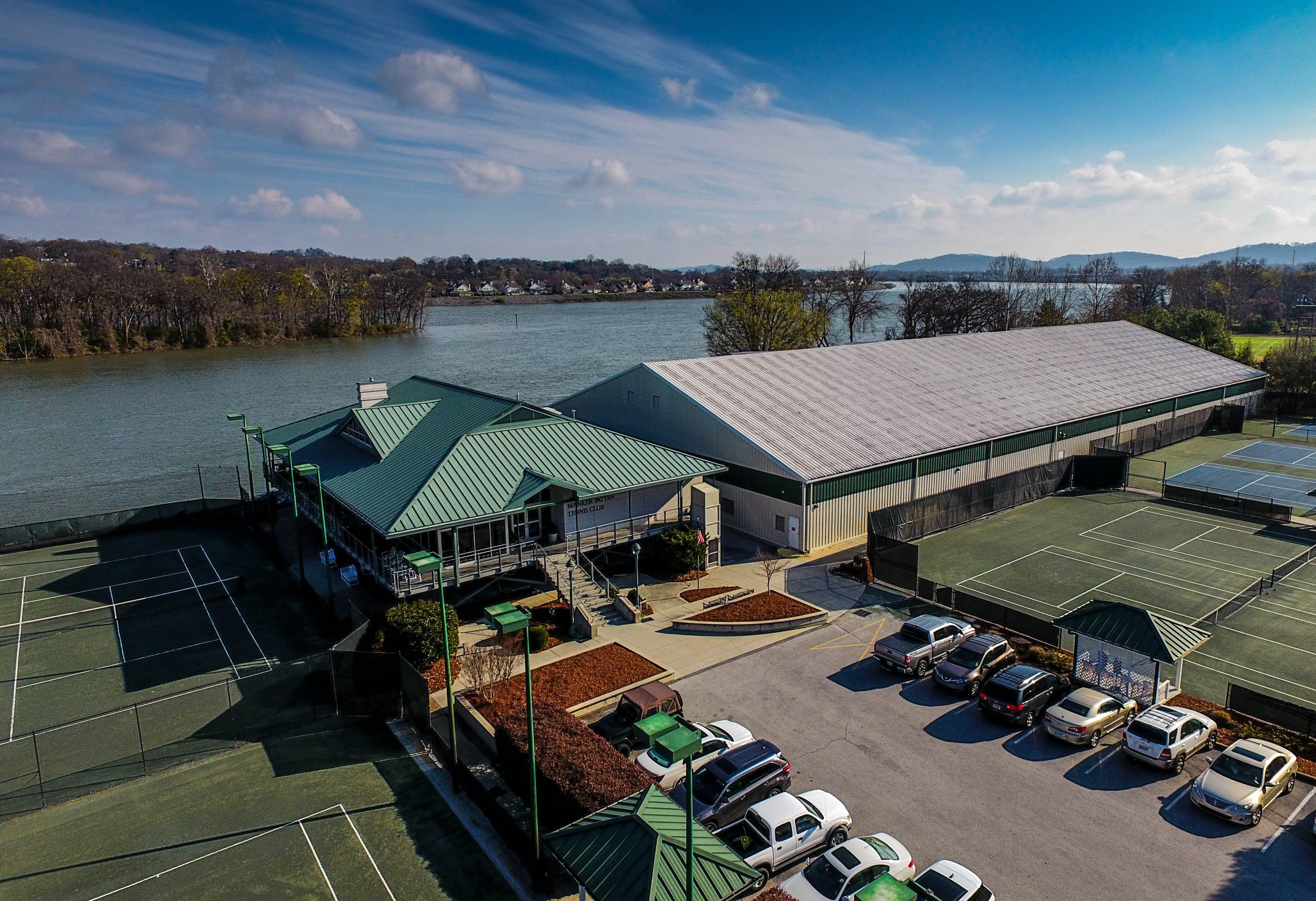 Manker Patten Tennis Club   In 2006 we completed a total renovation of the Zan Gurrey Clubhouse for the historical Manker Patten Tennis Club, located on the banks of the Tennessee River in Downtown Chattanooga, TN. This 6,000 square foot complex is complete with a full service pro shop, fitness room, lounge and dining area, and locker rooms. Not just a tennis complex, the scenic views and beautiful construction of Zan Gurrey Clubhouse is perfect for hosting a multitude of events including weddings, receptions, and private parties. In addition to this project, our past work for Manker Patten includes a 31,000 square foot indoor tennis facility located adjacent to the clubhouse that houses 5 hard courts.
