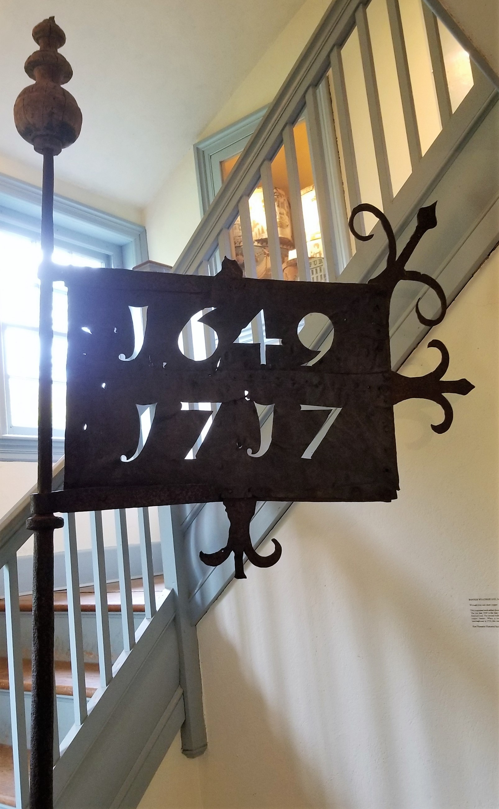 Banner Weather Vane, from the 1717 church, c. 1753  wrought iron and sheet cooper  This important local artifact documents the history of East Hampton's Meeting Houses. The top date 1649 is the date of construction of our first meeting house that had a thatched roof. The second building was built in 1717 memorialized by its date on this cooper banner. When a tower, clock, and steeple were added to the 1717 meetinghouse in 1753, this vane was constructed to honor the churches' lineage.  East Hampton Historical Society